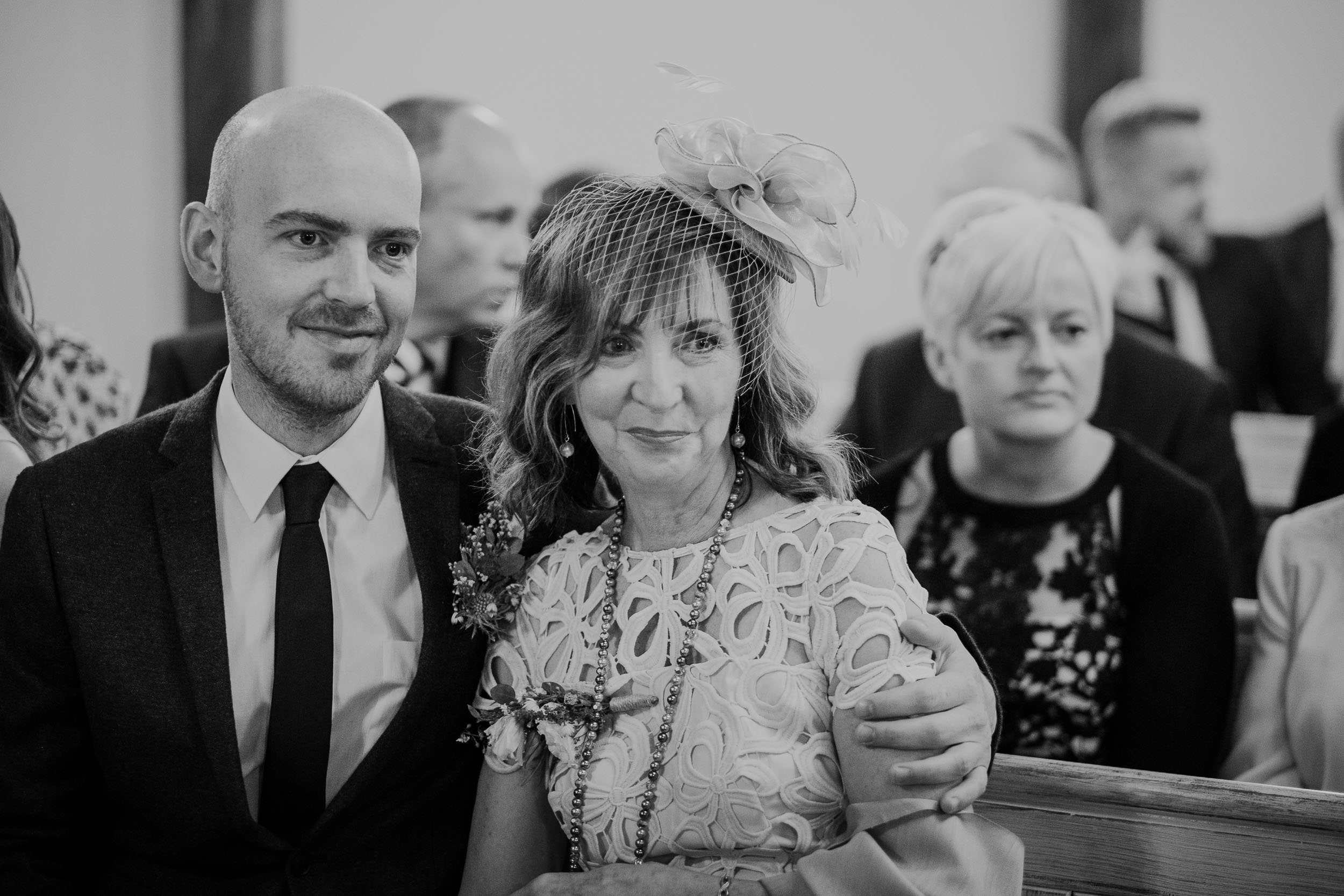 Son hugs his mother during an emotional wedding ceremony in a black and white photograph