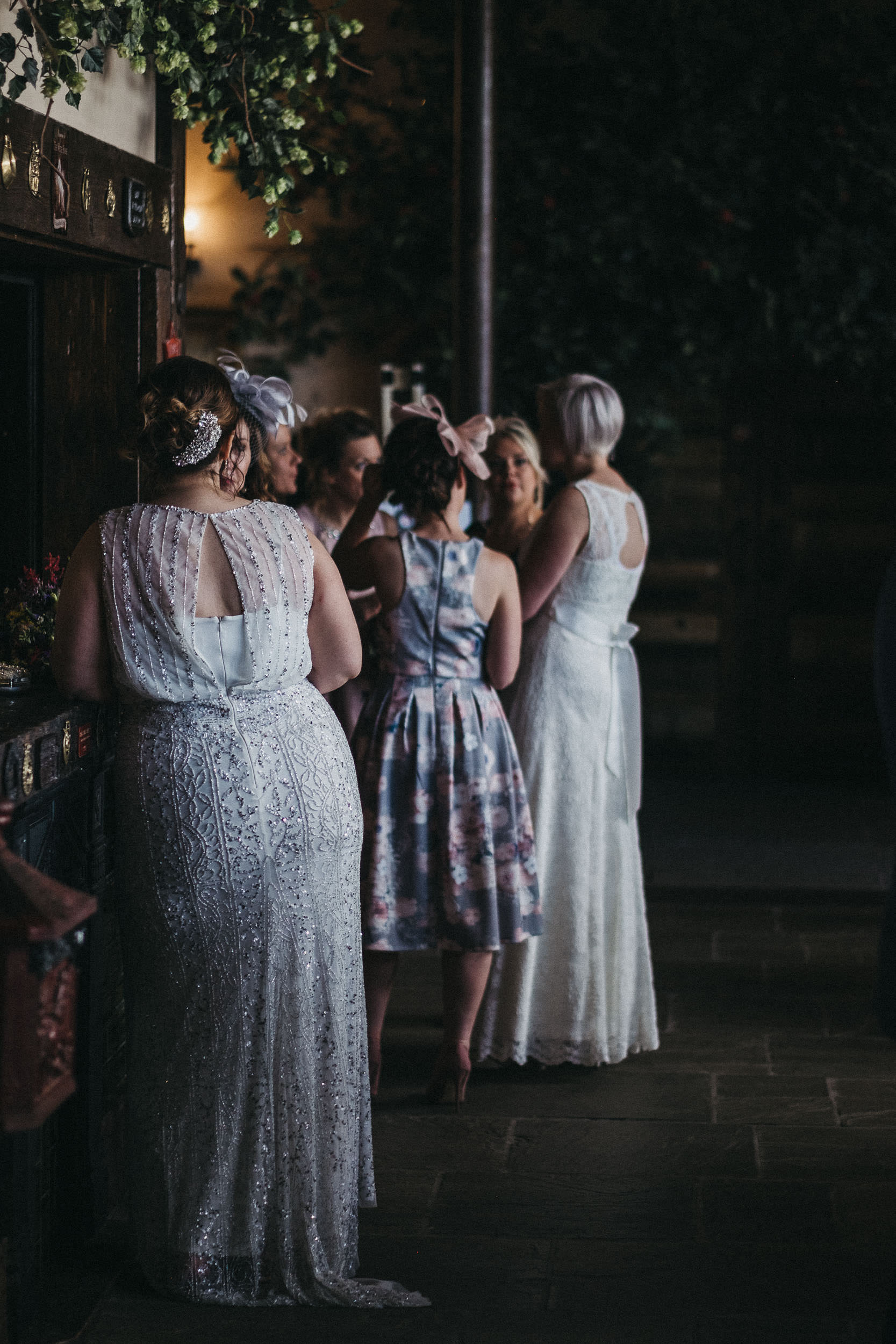 One bride leans on bar while looking at another bride talking with wedding guests
