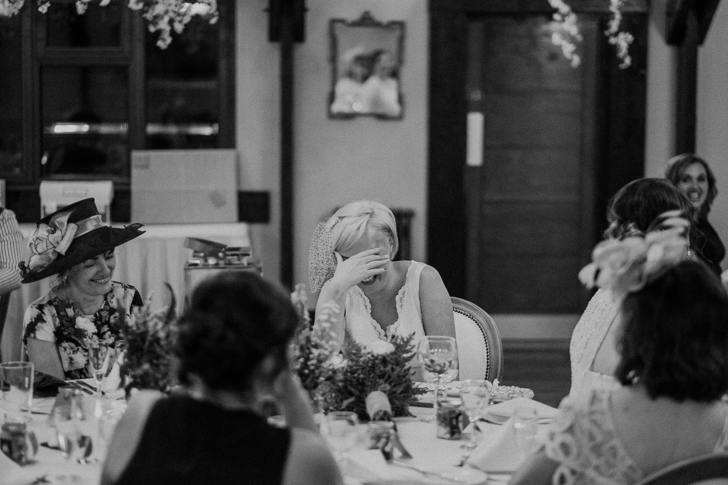 Black and white photo of the bride holding her head in her hands during the speeches at her wedding