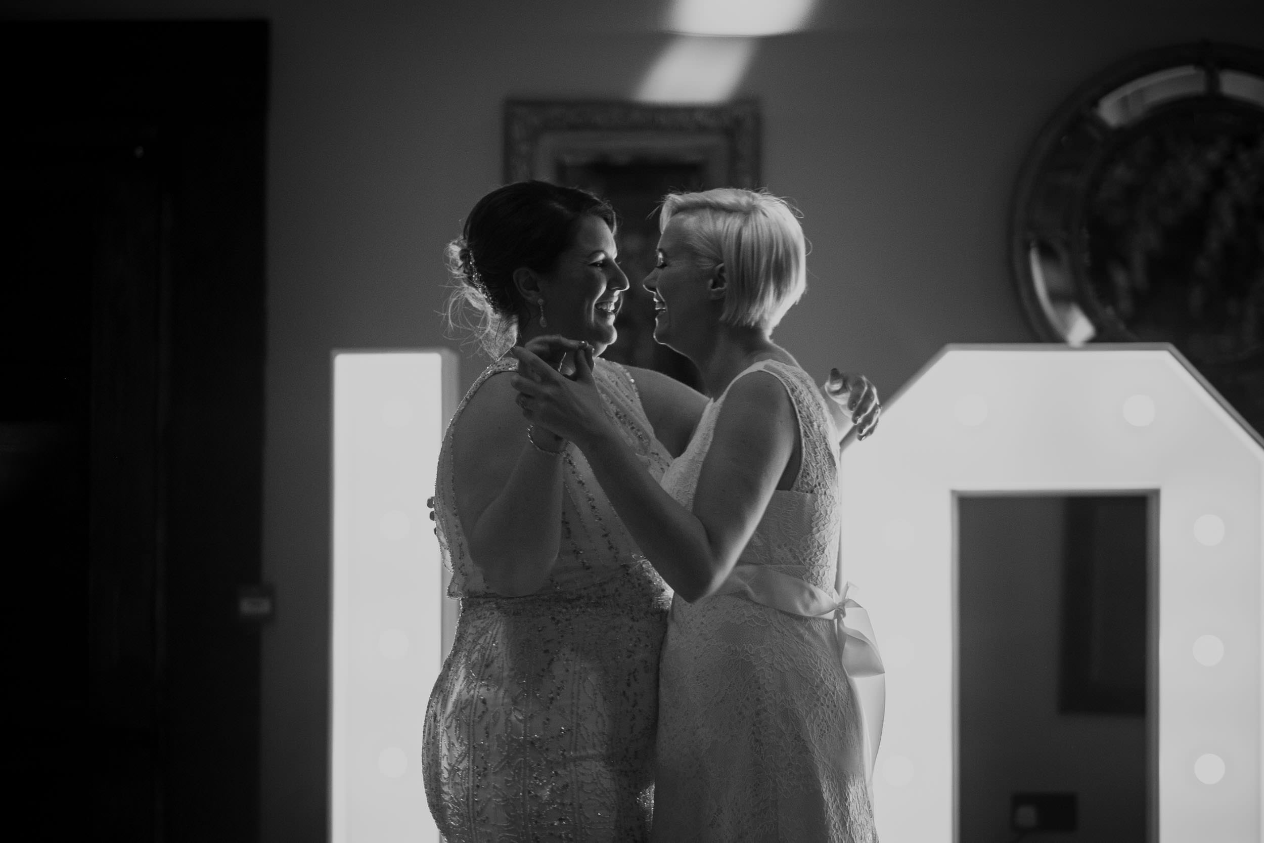 Two brides laugh during the first dance in a romantic black and white photo