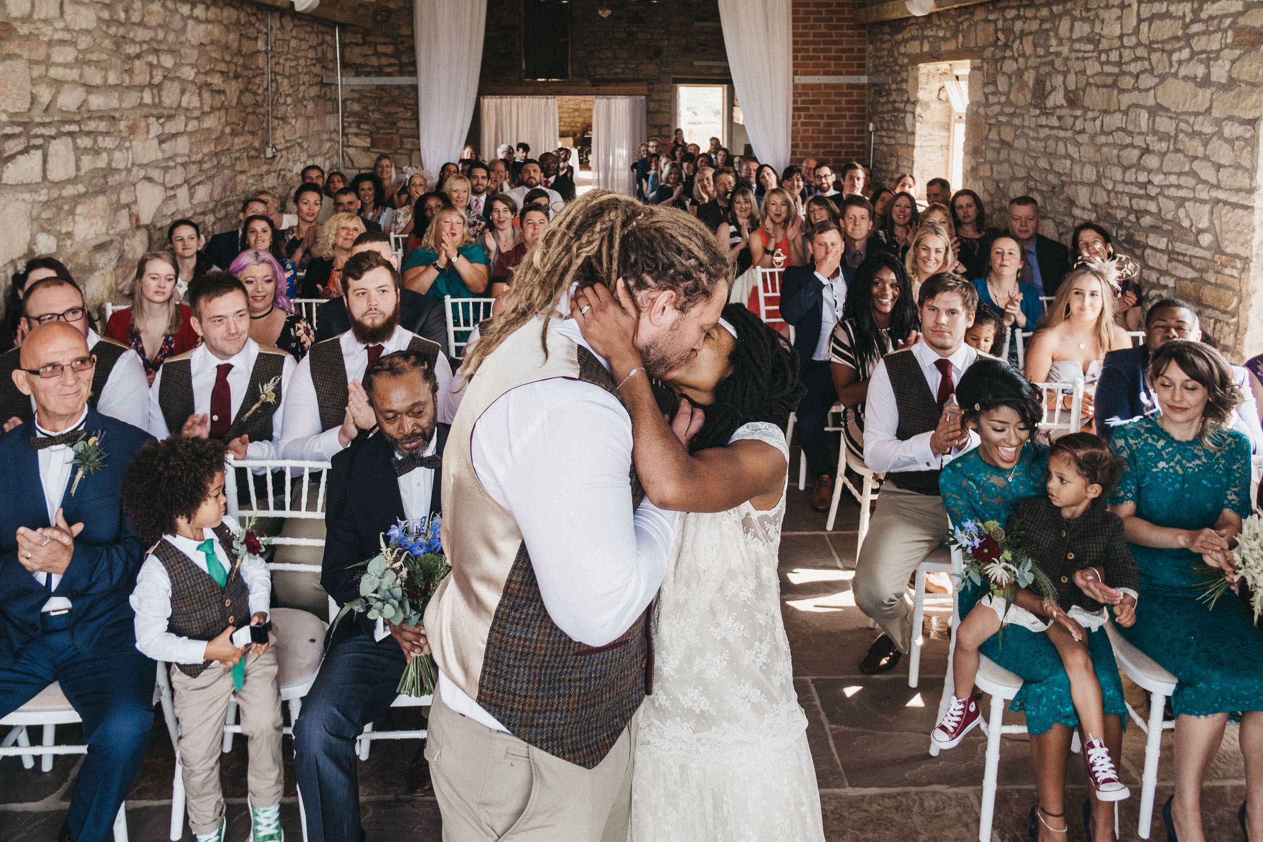 Bride and groom kiss in front of their guests at a farm wedding in Newcastle