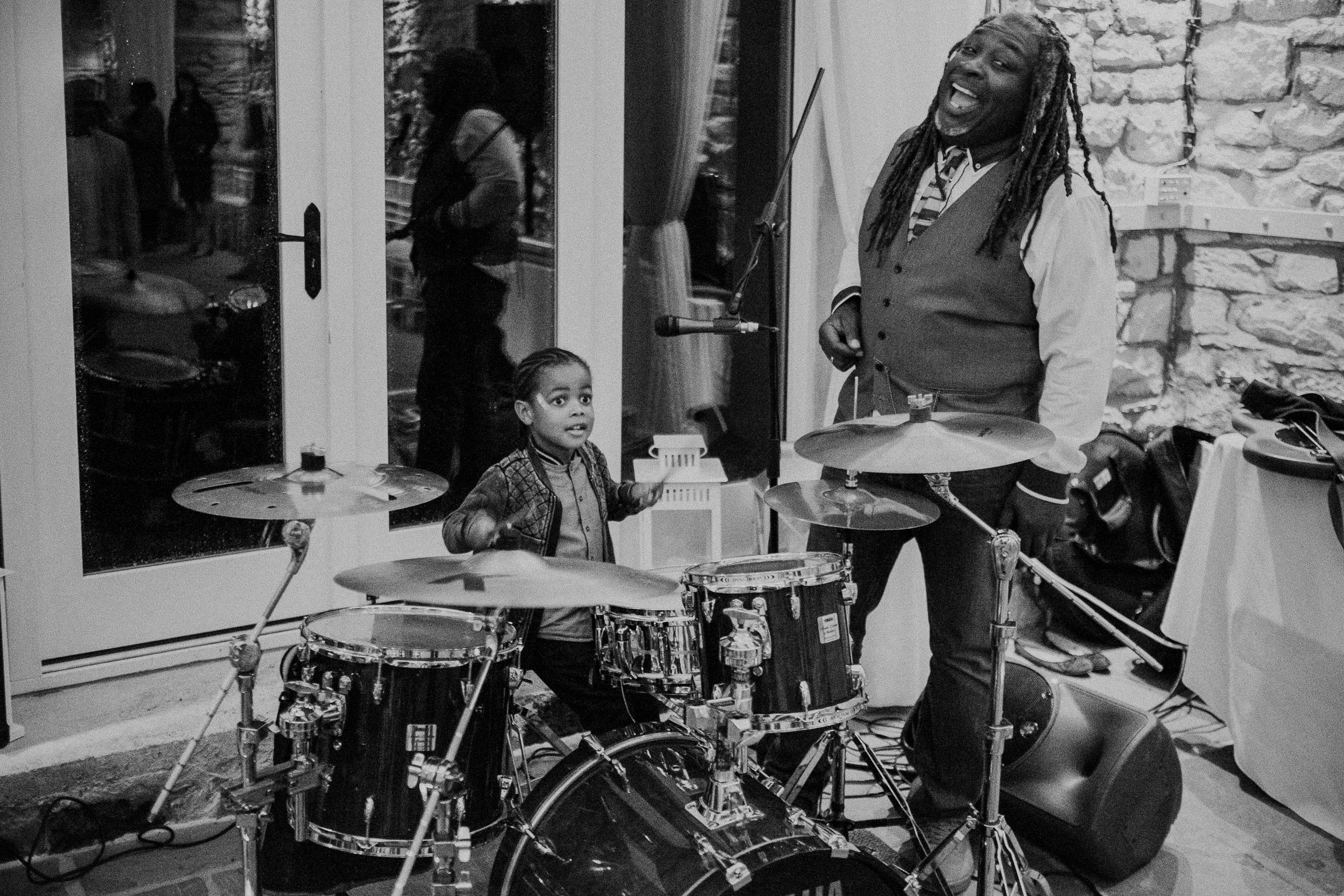 Black and white photo of young wedding guest drumming while man with dreadlocks watches