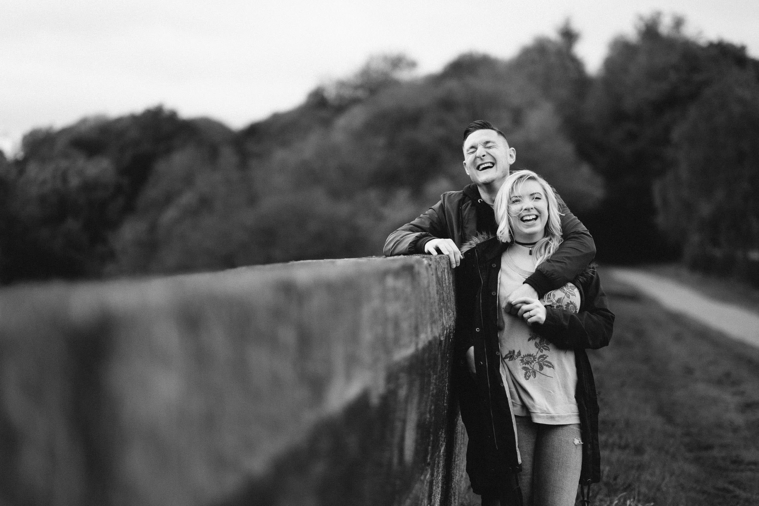 Black and white photo of couple laughing during pre-wedding shoot at Derwent Walk