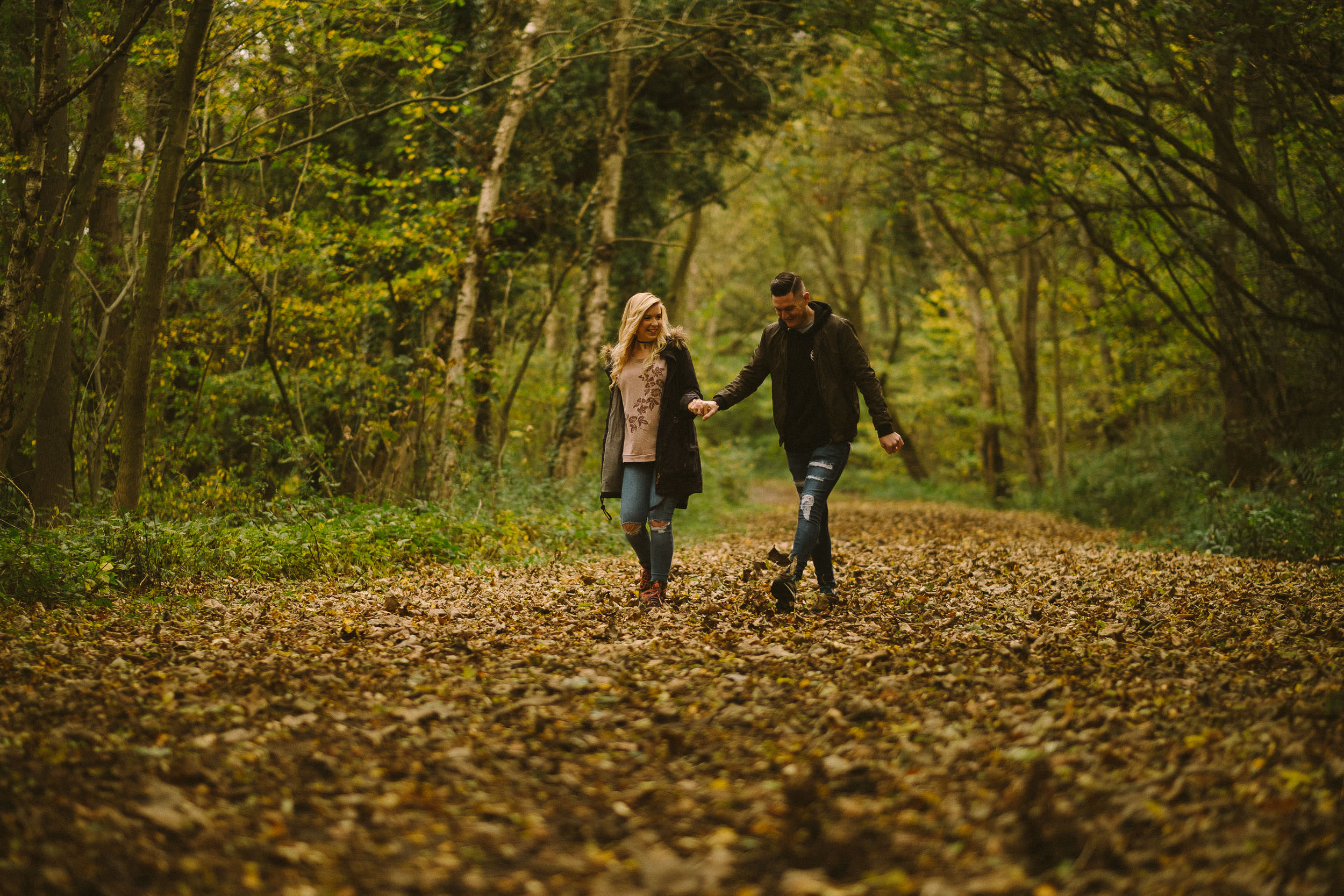Couple hold hands as they walk through autumn leaves on Derwent Walk