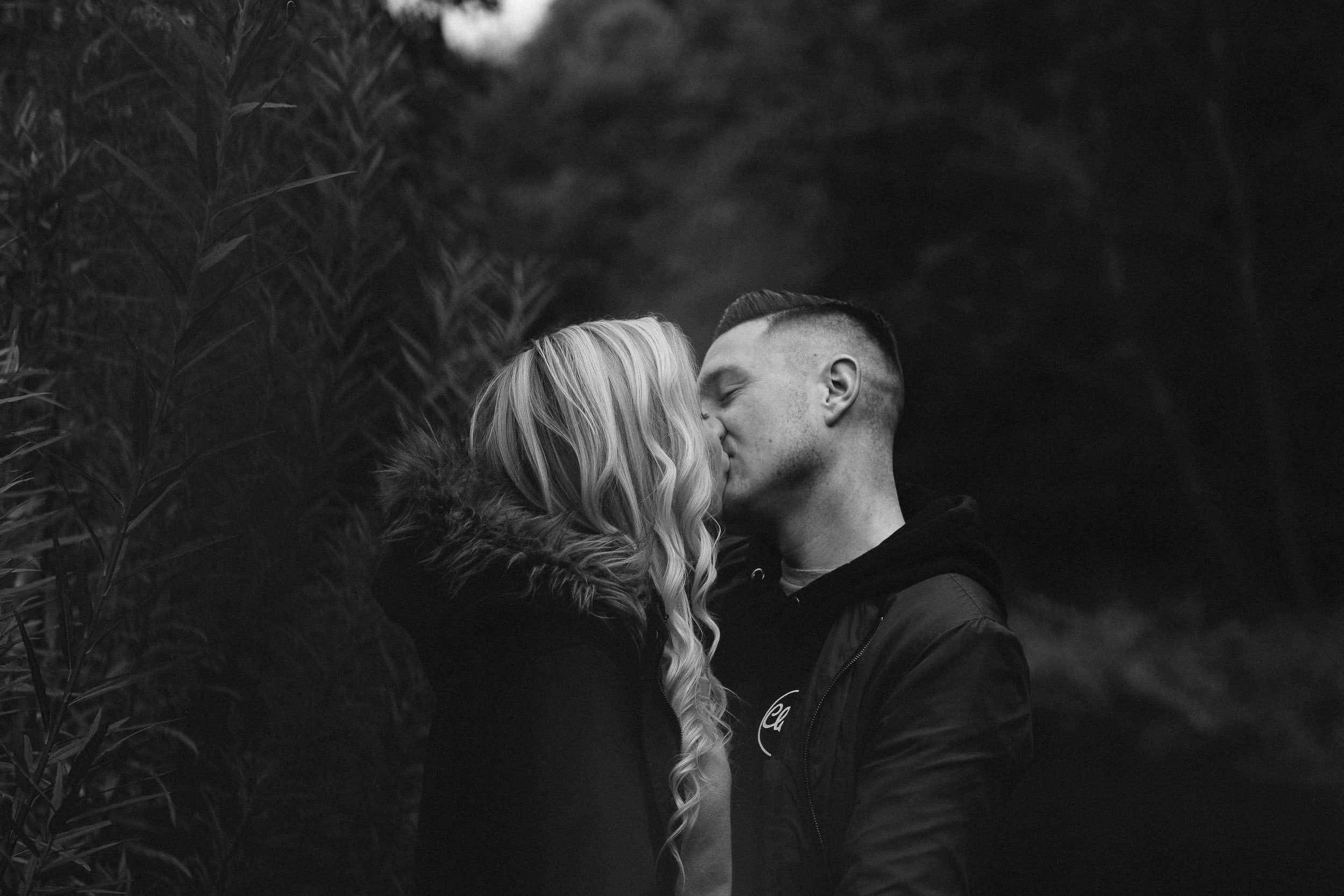 Sexy black and white photo of couple kissing on pre-wedding shoot
