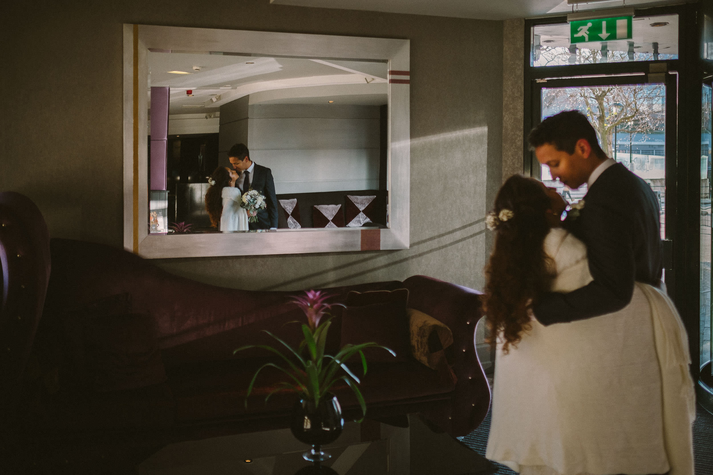 Bride and groom kiss while reflected in mirror at Malmaison Newcastle