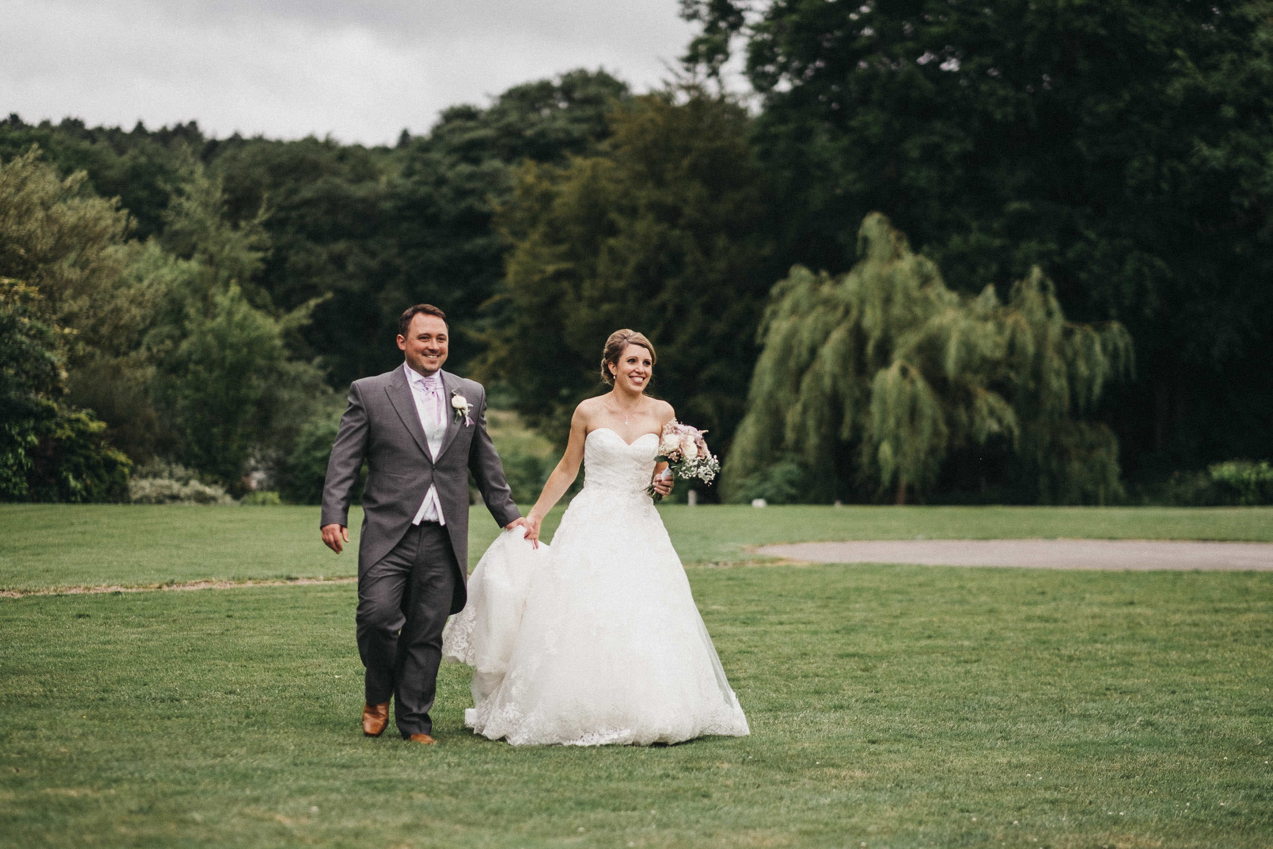Bride and groom laugh as they walk across grounds of Yorkshire wedding venue