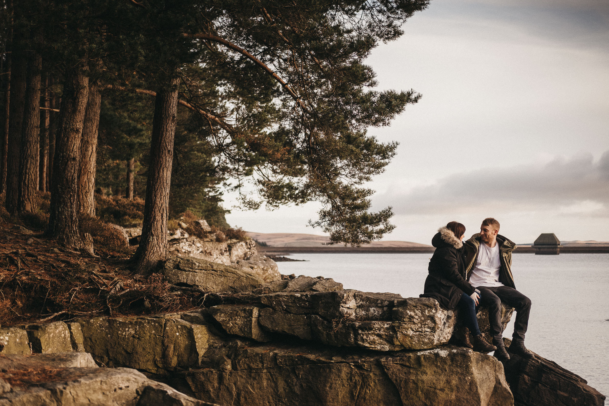 Bride and groom to be sit on a rock looking over Kielder Reservoir during a pre wedding session