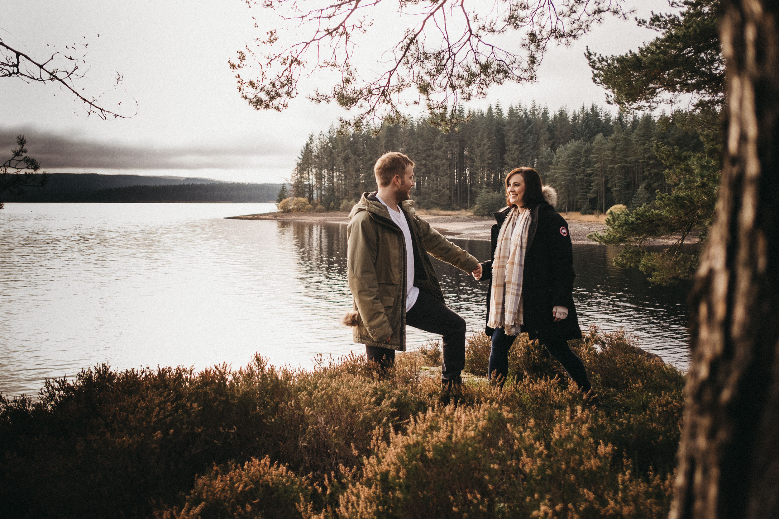 Couple hold hands on a moss covered rock with Kielder Water behind