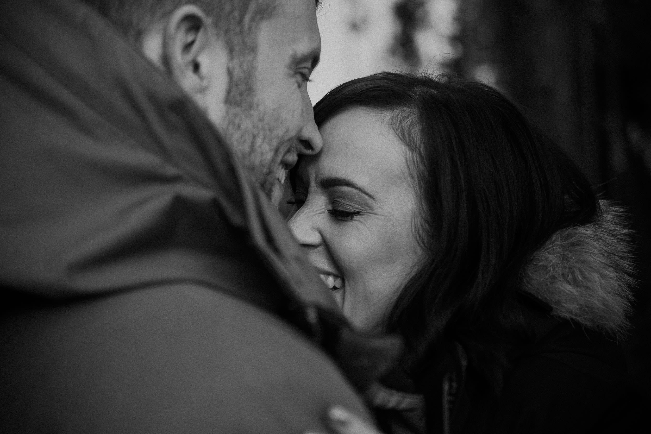 Black and white photo of couple embracing with the girl laughing