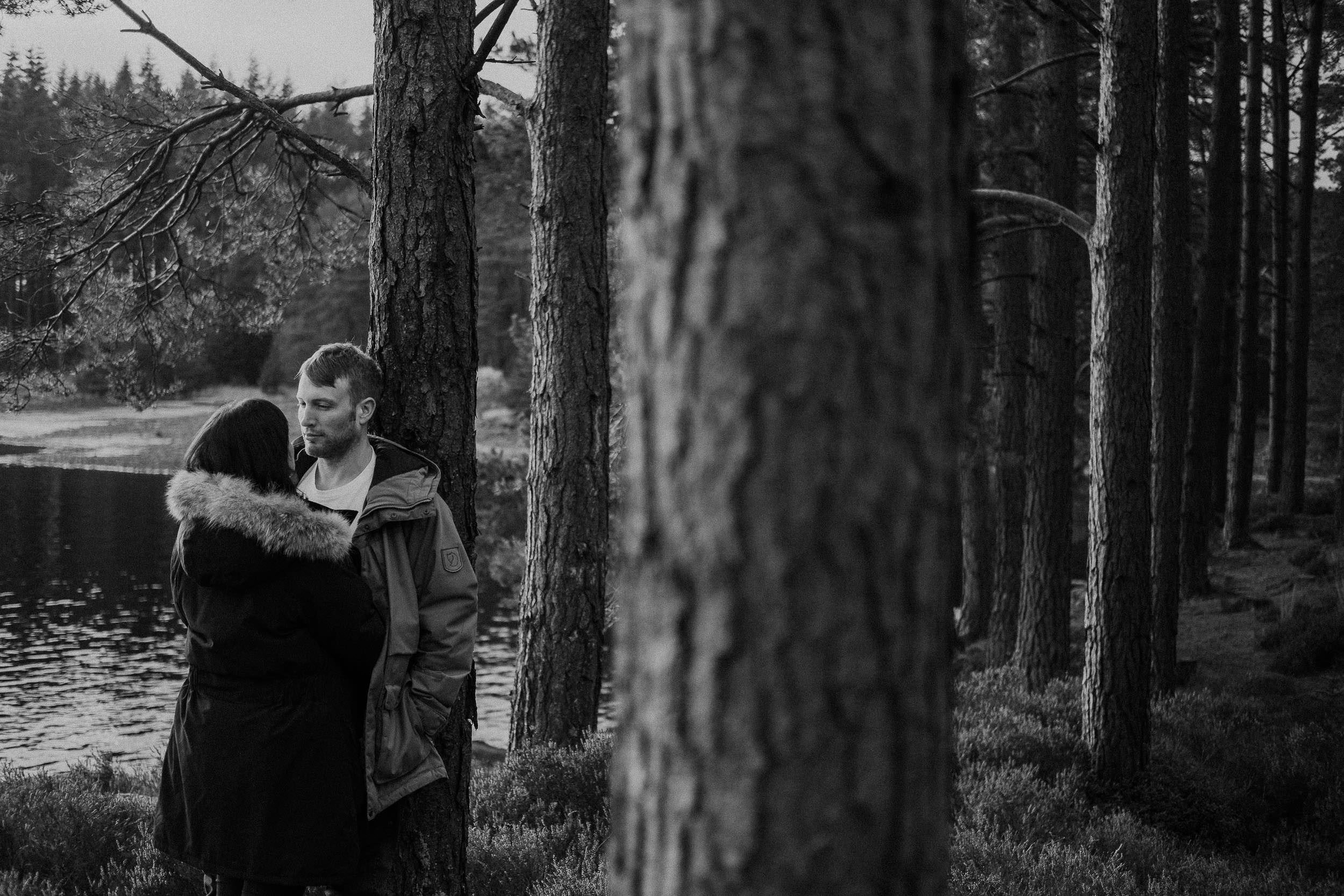 Black and white photo of a couple cuddling in Kielder Forest