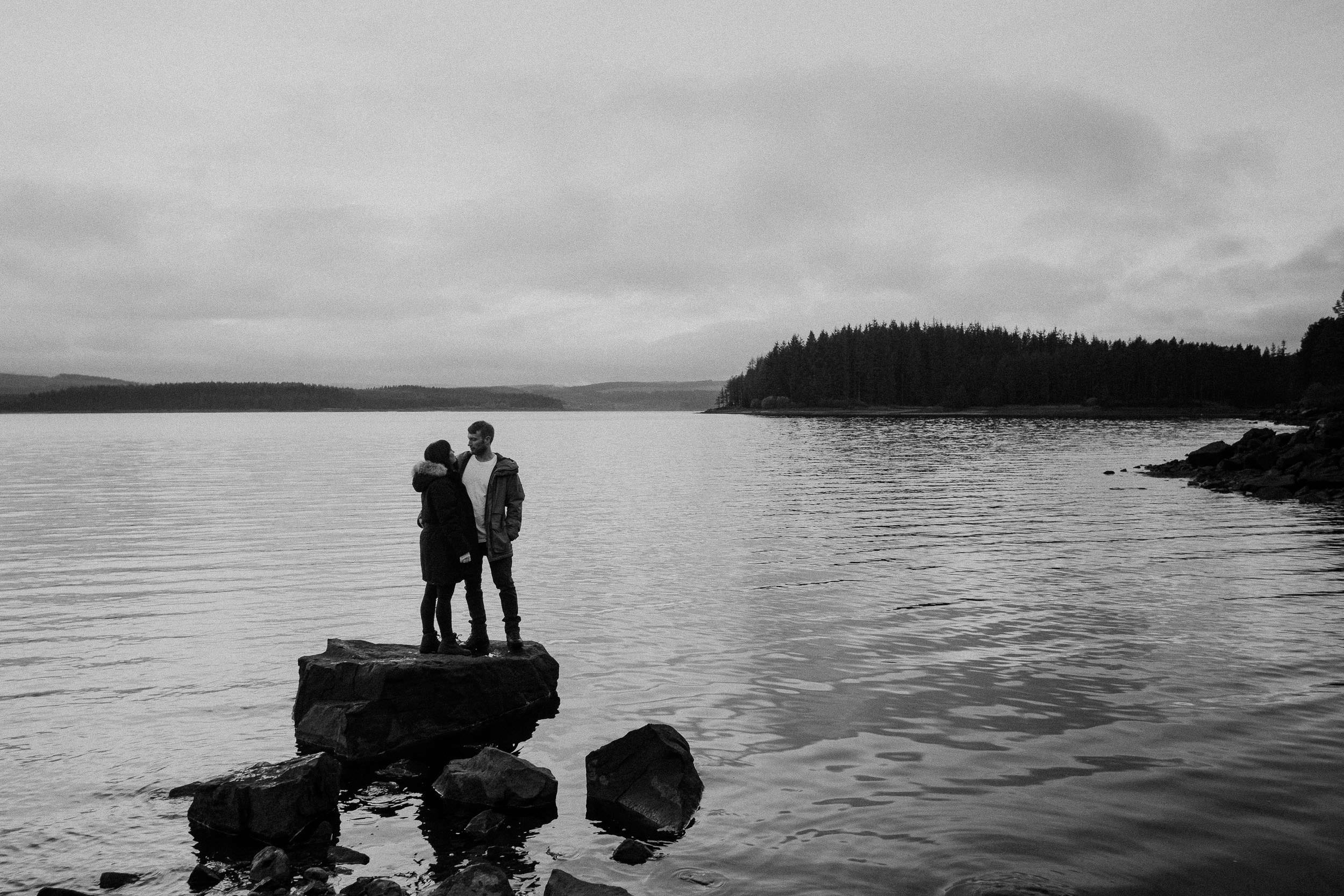 Black and white photo of a couple standing on a rock in Kielder water