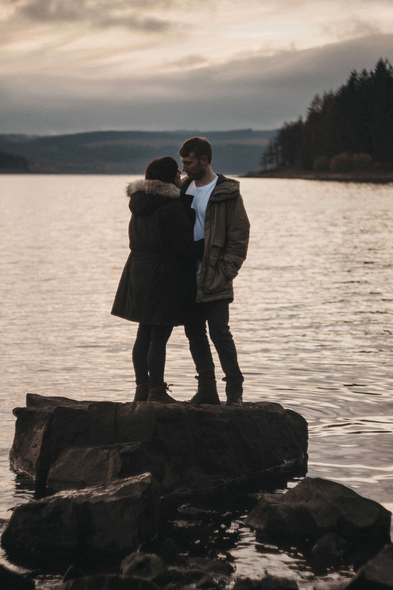 A couple stand on a rock in Kielder Reservoir at sunset