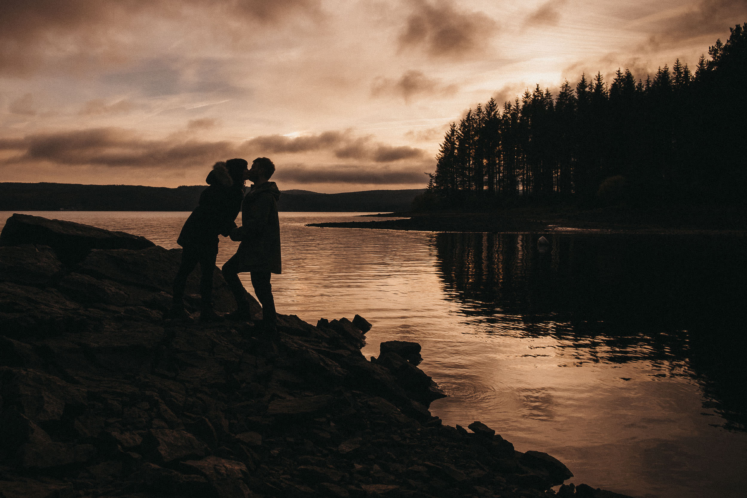 Silhouettes of a couple kissing at sunset with Kielder water and forest behind them