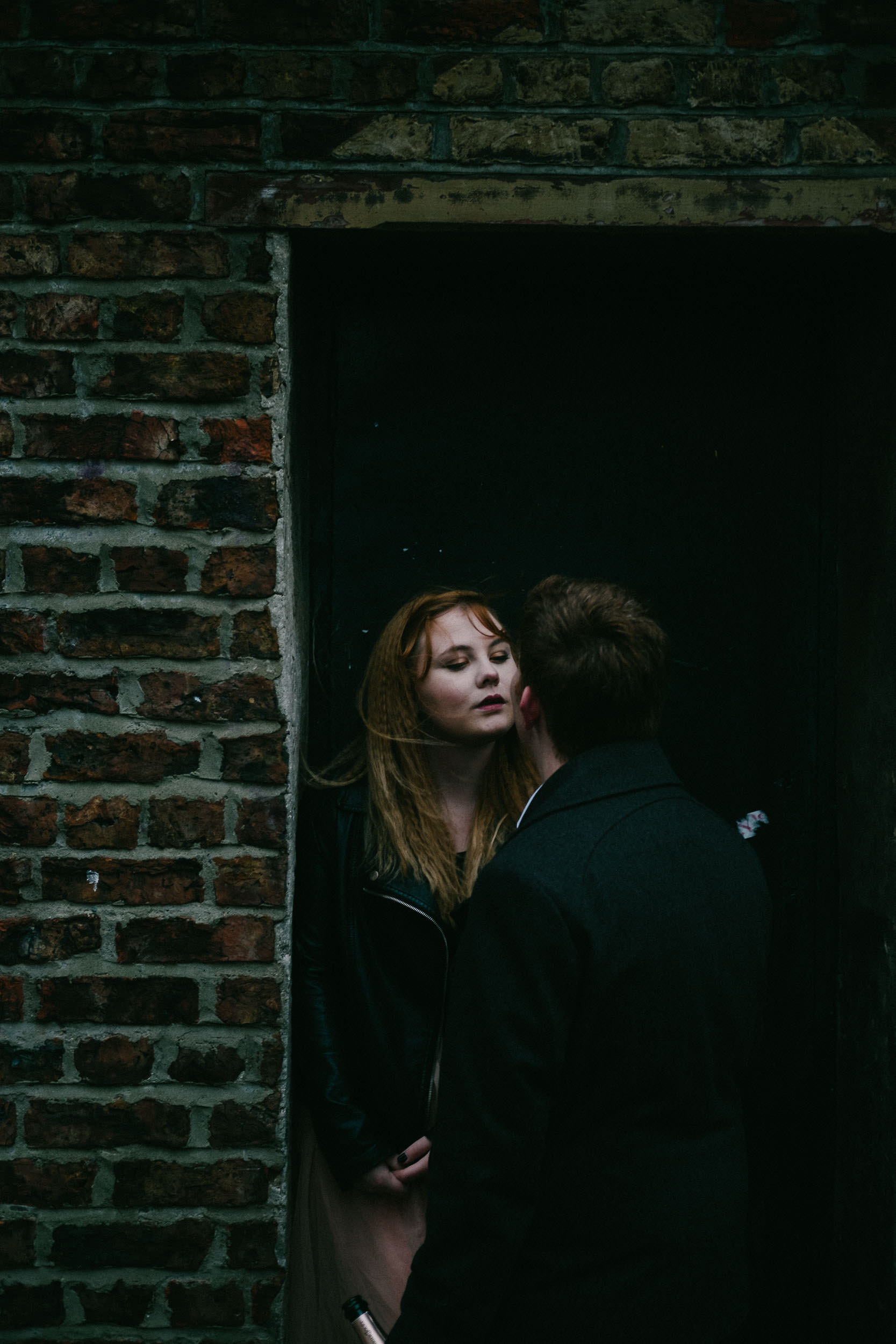 Engaged couple look at each other intensely in a brick doorway