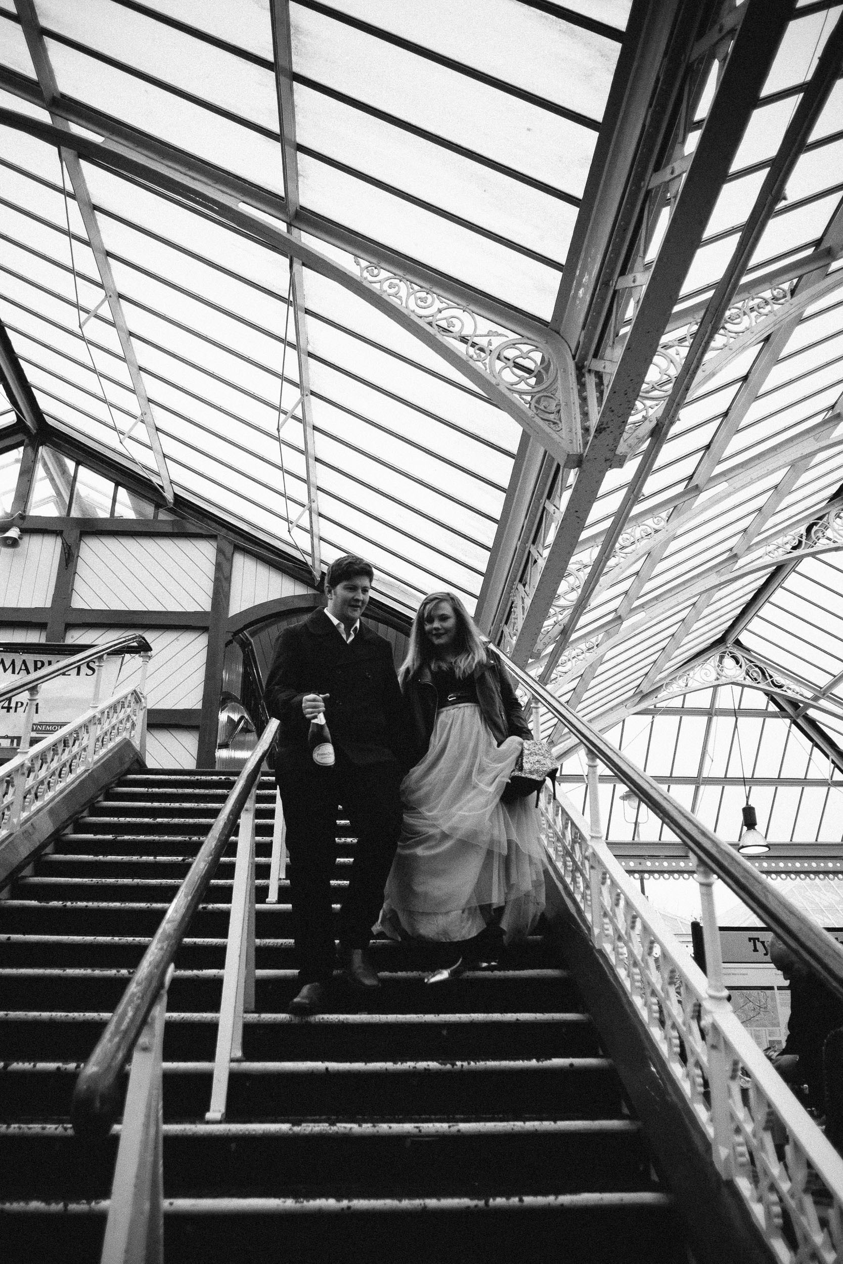 Black and white photo of a couple walking down stairs at Tynemouth Metro station