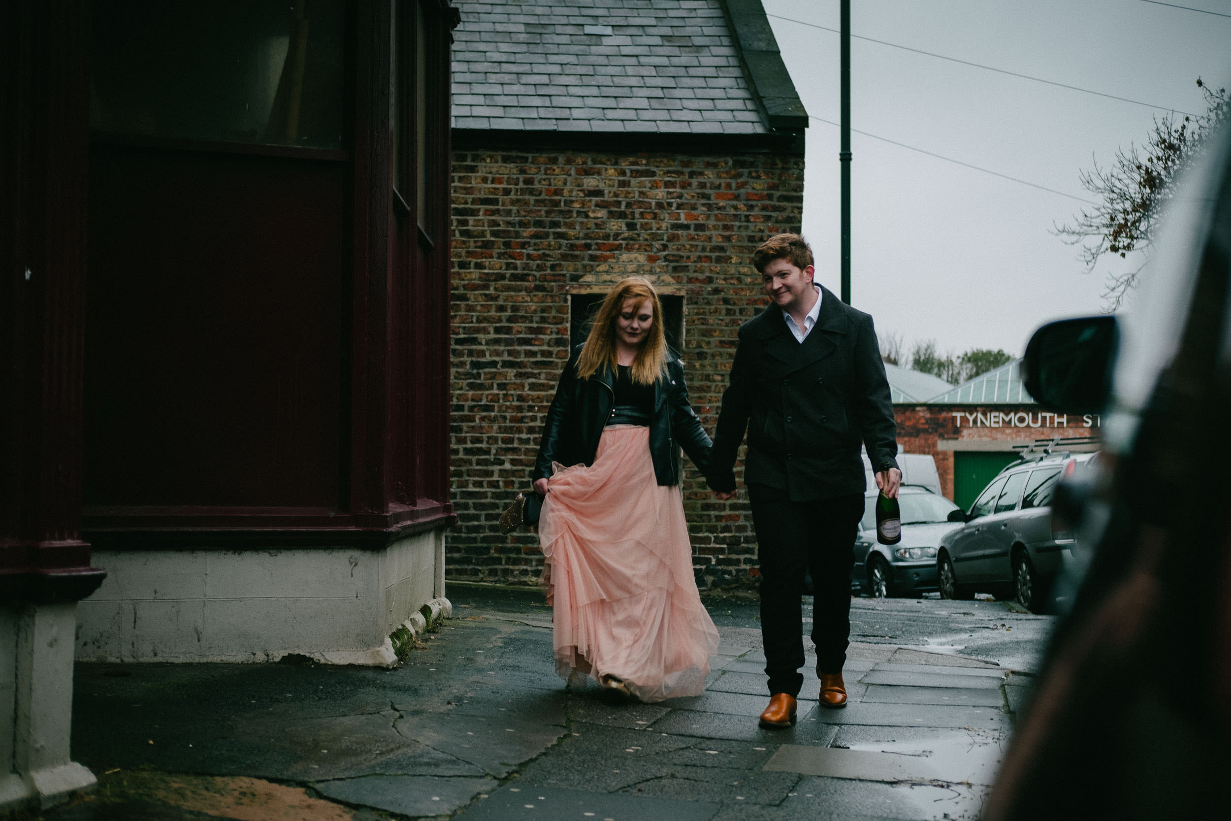Couple walk through the rainy streets of Tynemouth holding a champagne bottle