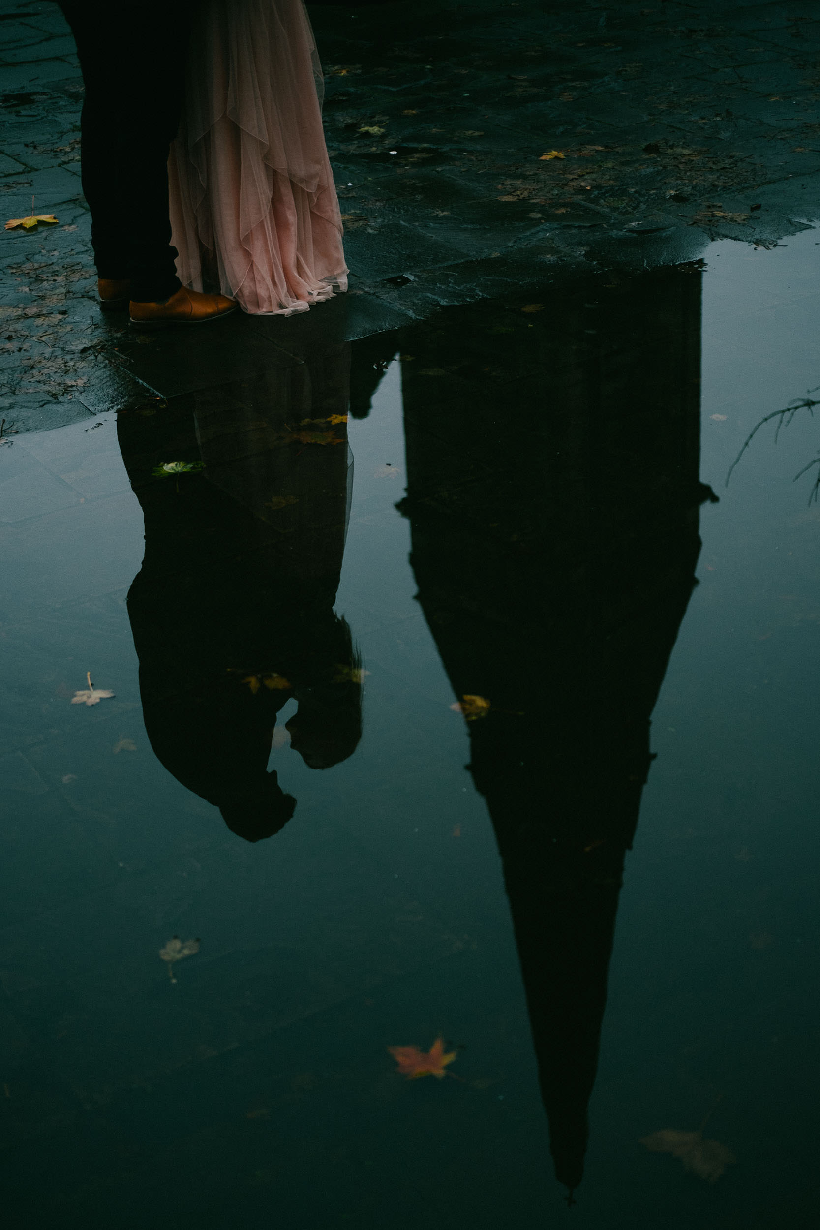 Reflection of pre-wedding couple cuddling in puddle with church spire