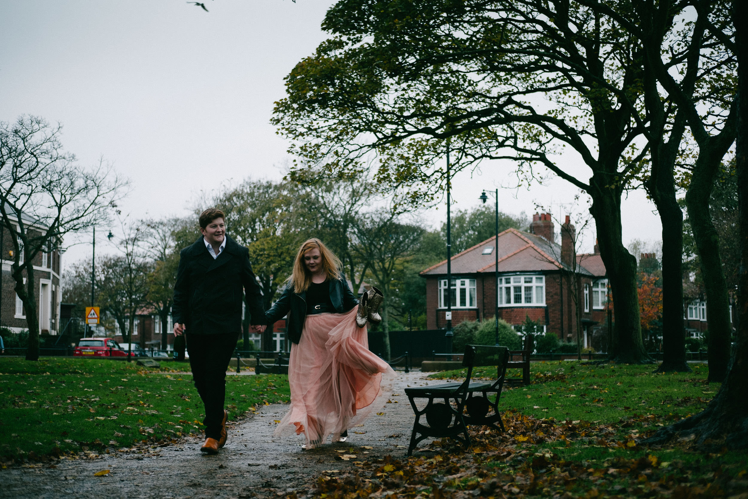 Engaged couple walk through wet park at Tynemouth