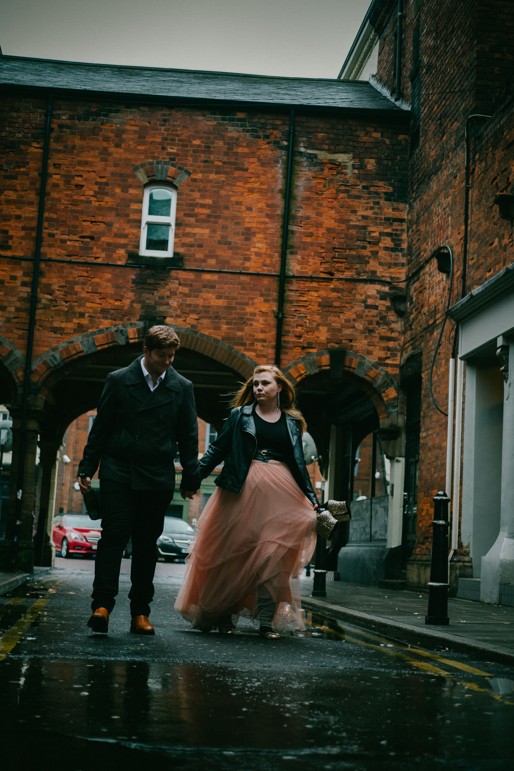 Couple walk up rainy alleyway with girl's dress blowing in wind
