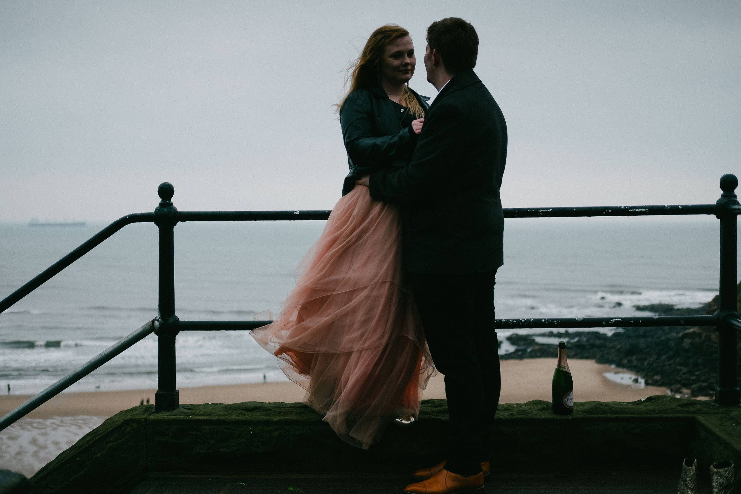 Wind blows girl's dress as couple cuddle at beach