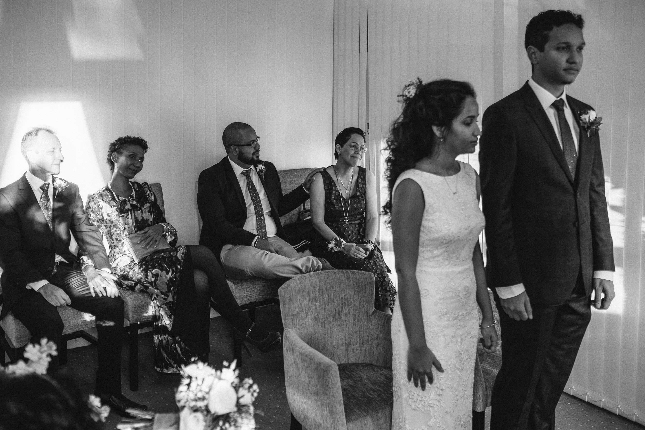 Black and white photo of bride and groom with parents in background during ceremony