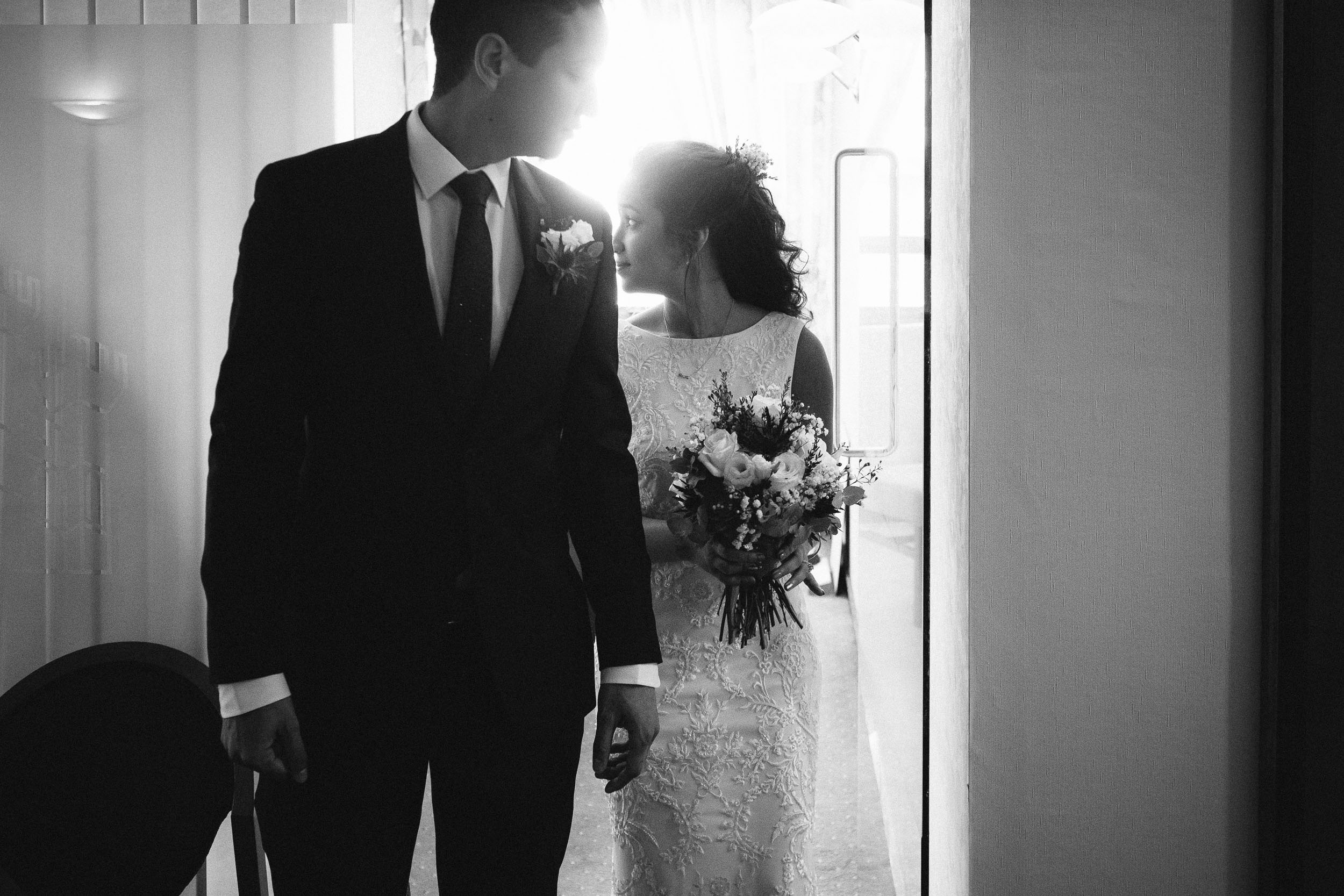 Black and white photo of bride and groom leaving wedding ceremony