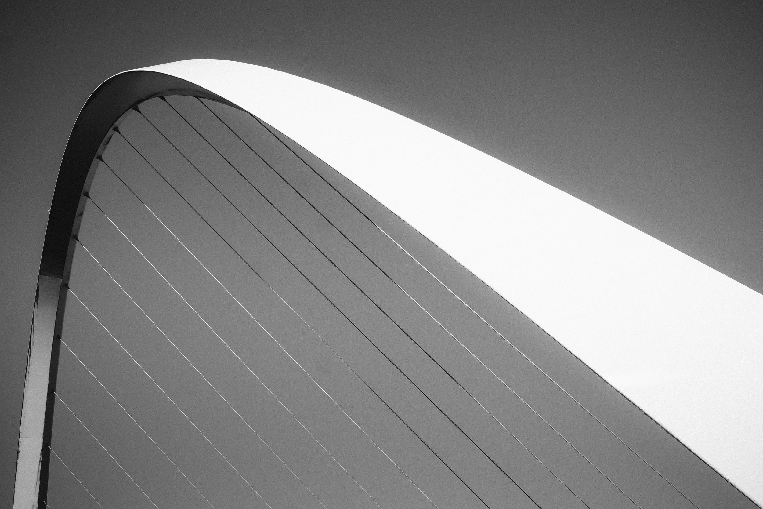Black and white photo of the arch of the Millennium bridge Newcastle Gateshead