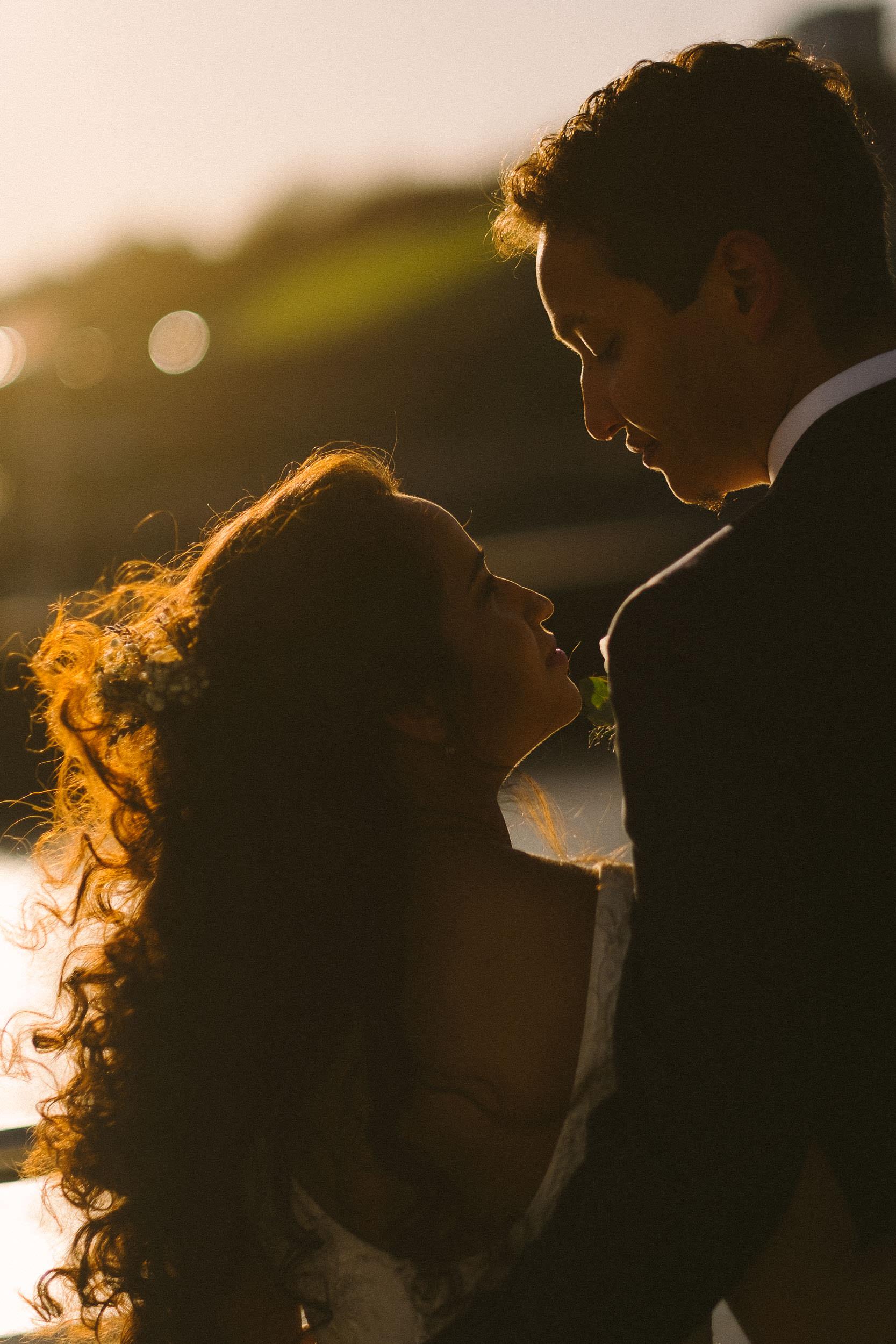 Bride and groom embrace on Quayside in warm winter sun