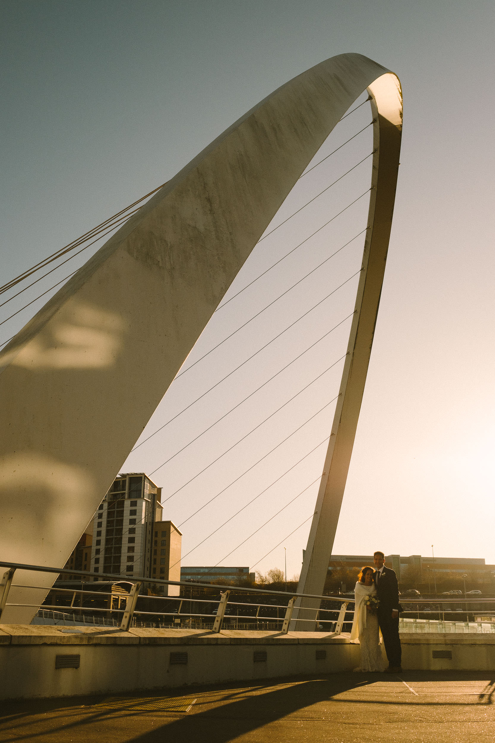 Bride and groom pose underneath the arch of the Millennium Bridge