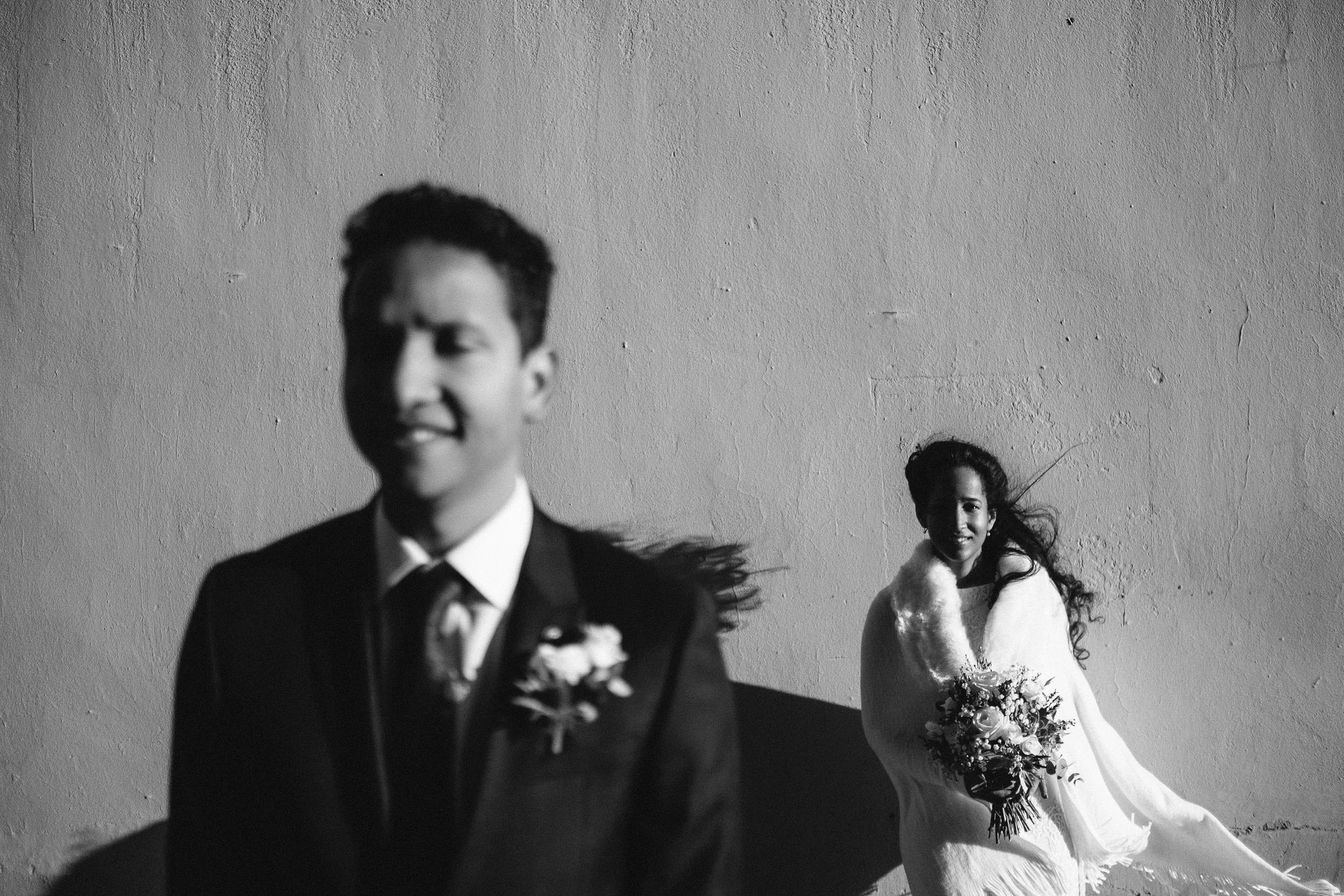 Black and white photo of bride and groom in harsh winter light with deep shadows