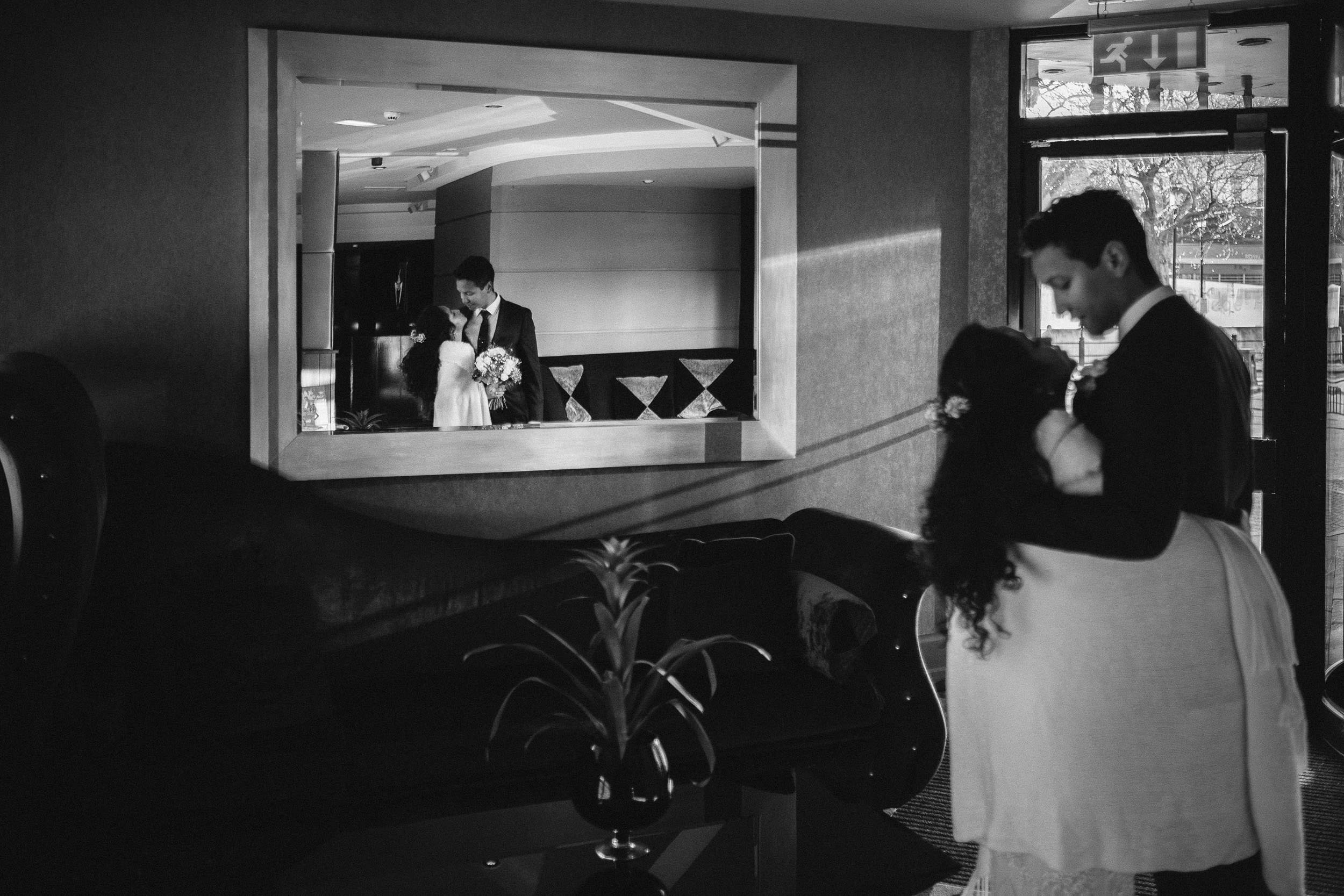 Bride and groom kiss in Malmaison reception in black and white