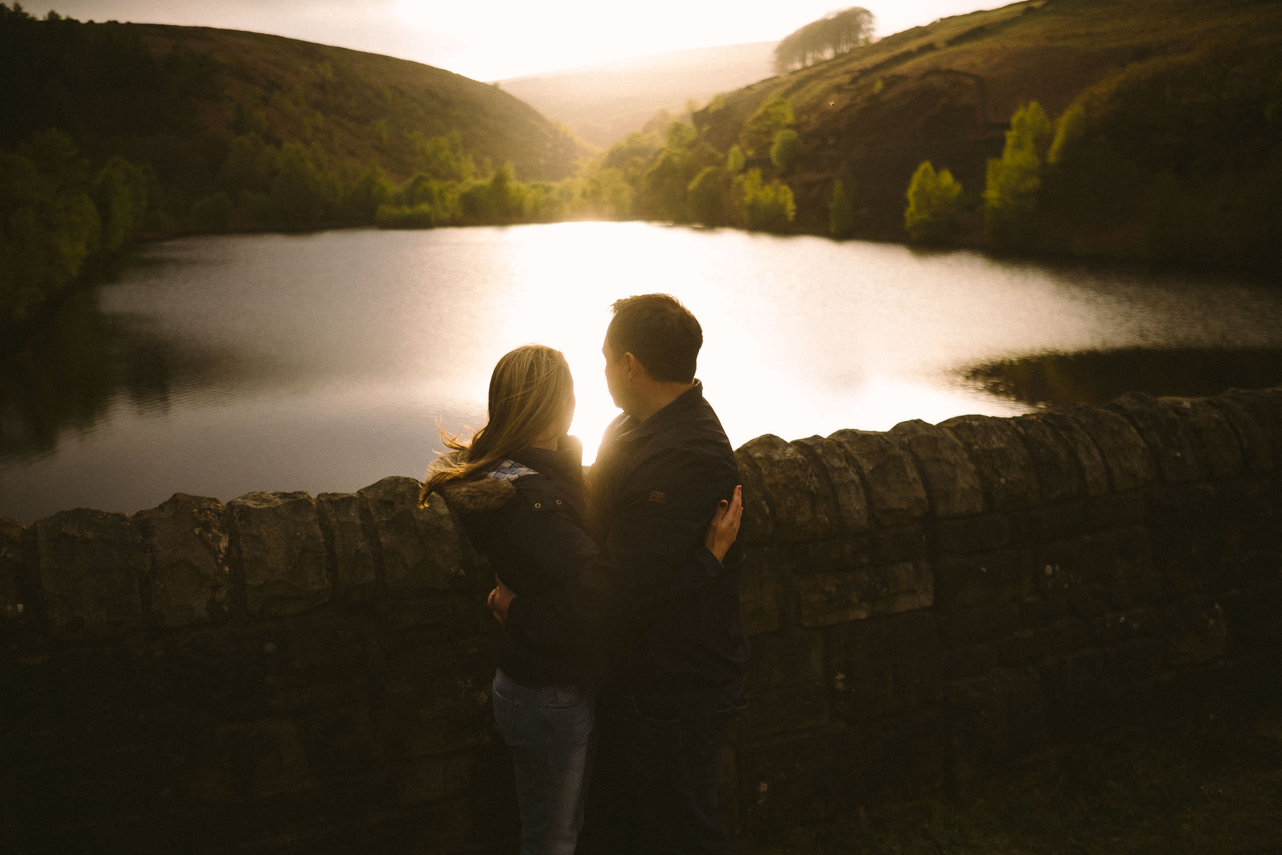 Couple embrace and look out over Digley reservoir as the sun shines off the water