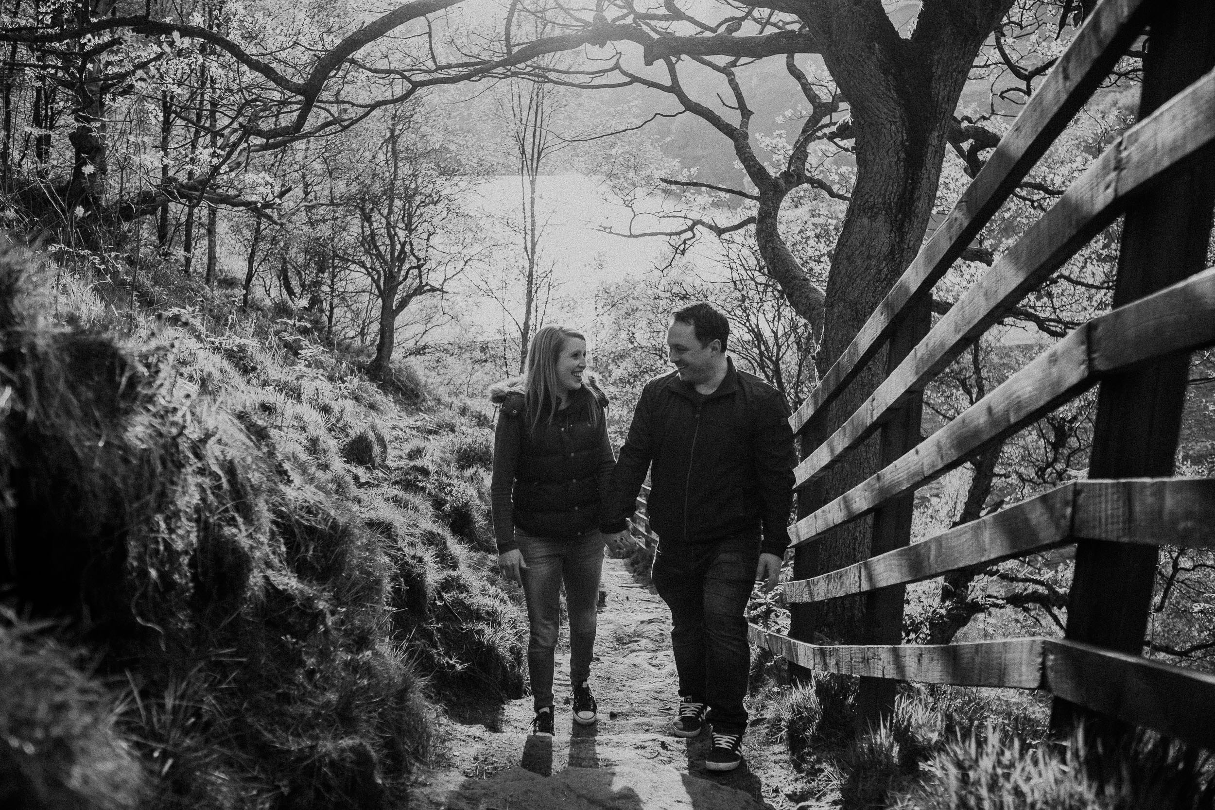 Black and white photo of a couple walking up a steep path holding hands