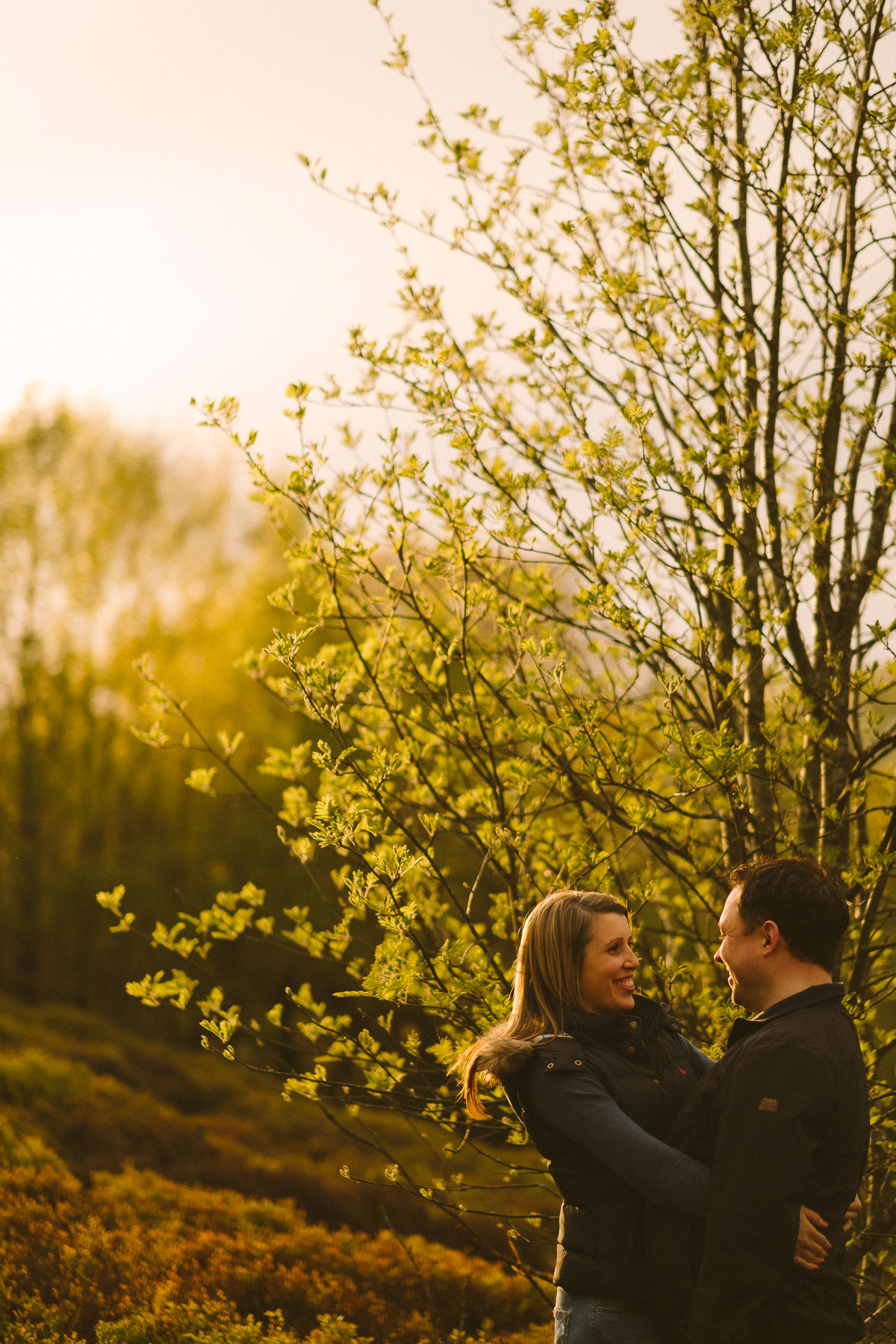 Backlit photo of couple laughing with small tree behind