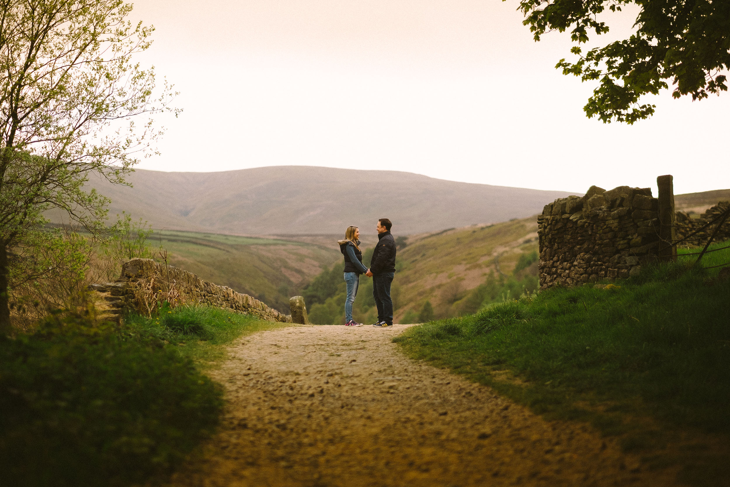 Couple hold hands on country path with distant hills behind them