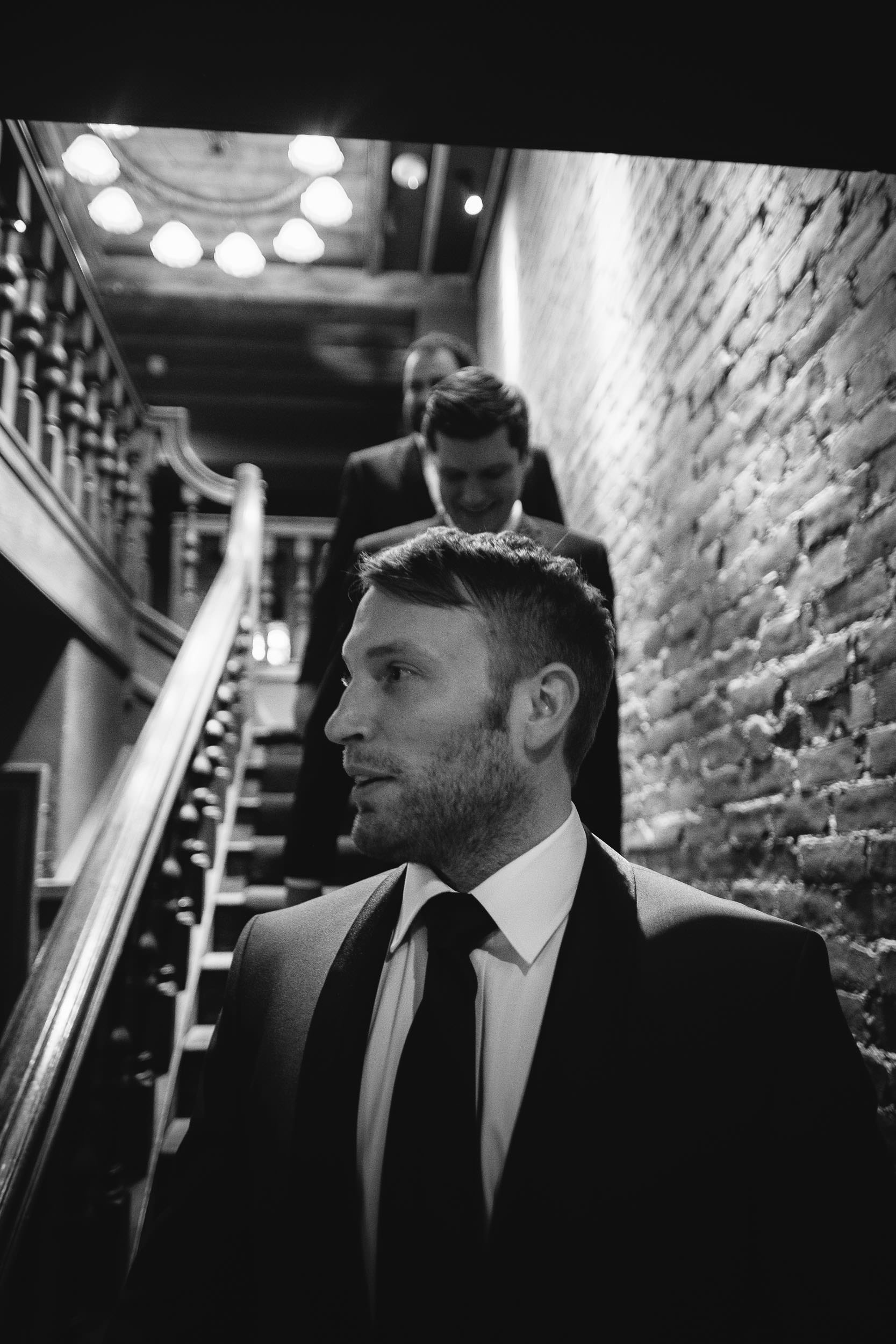 Black and white photo of the groom and groomsmen walking down stairs to ceremony