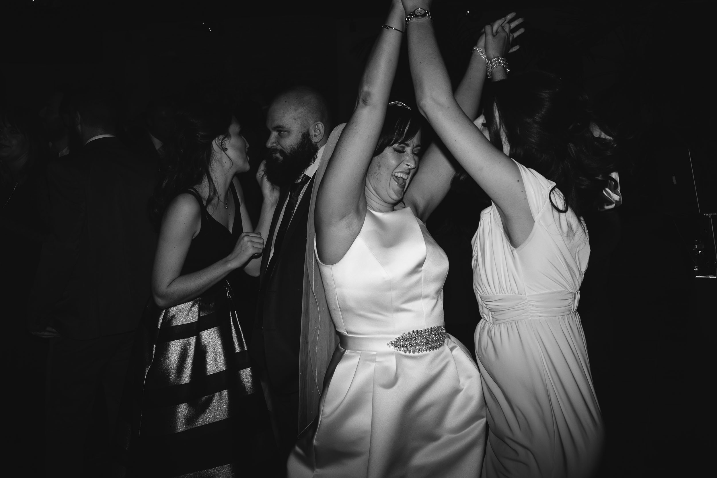 Black and white photo of bride and bridesmaid dancing
