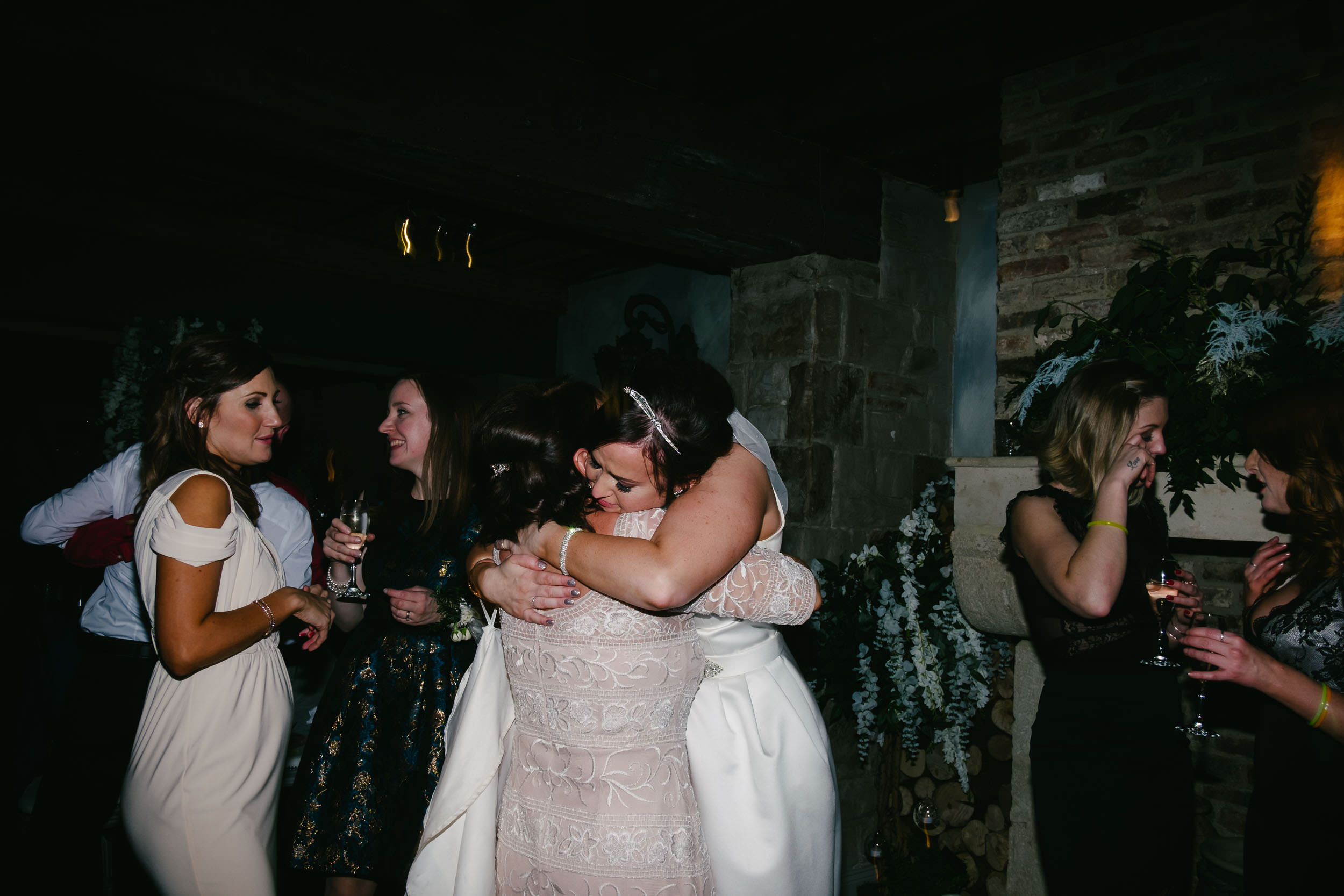 Bride hugs mother close at wedding