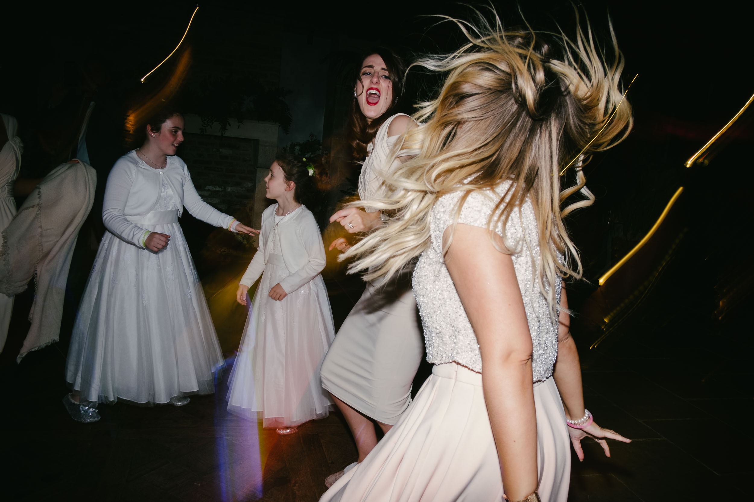 Bridesmaids dance with hair flying at Le Petit Château