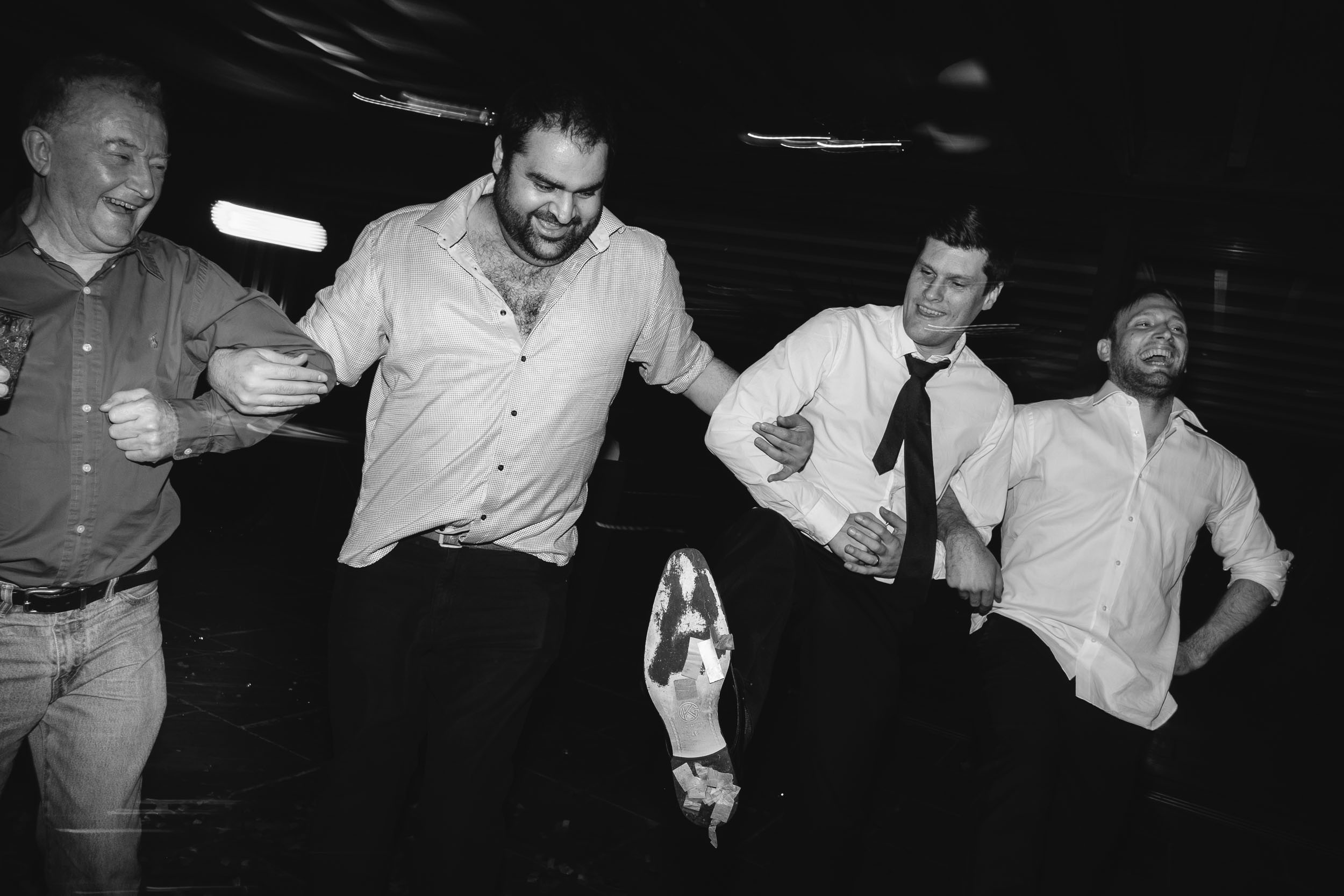 Black and white photo of groomsmen line dancing at wedding