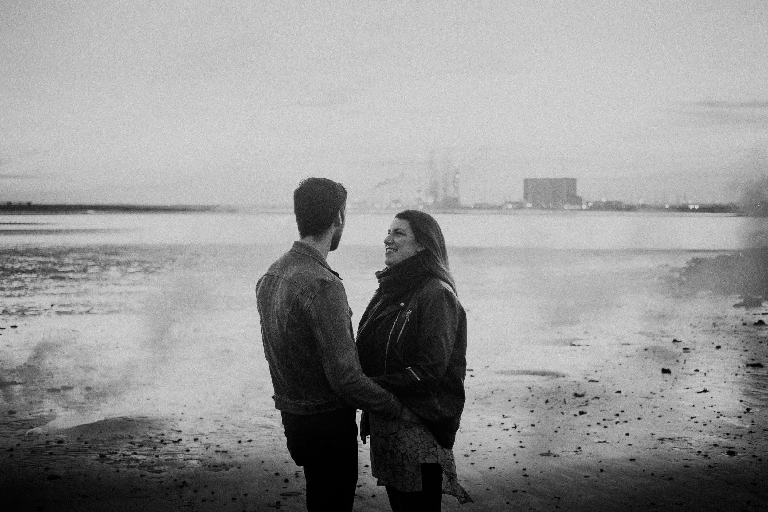 black and white photo of couple holding hands at South Gare beach on pre-wedding shoot