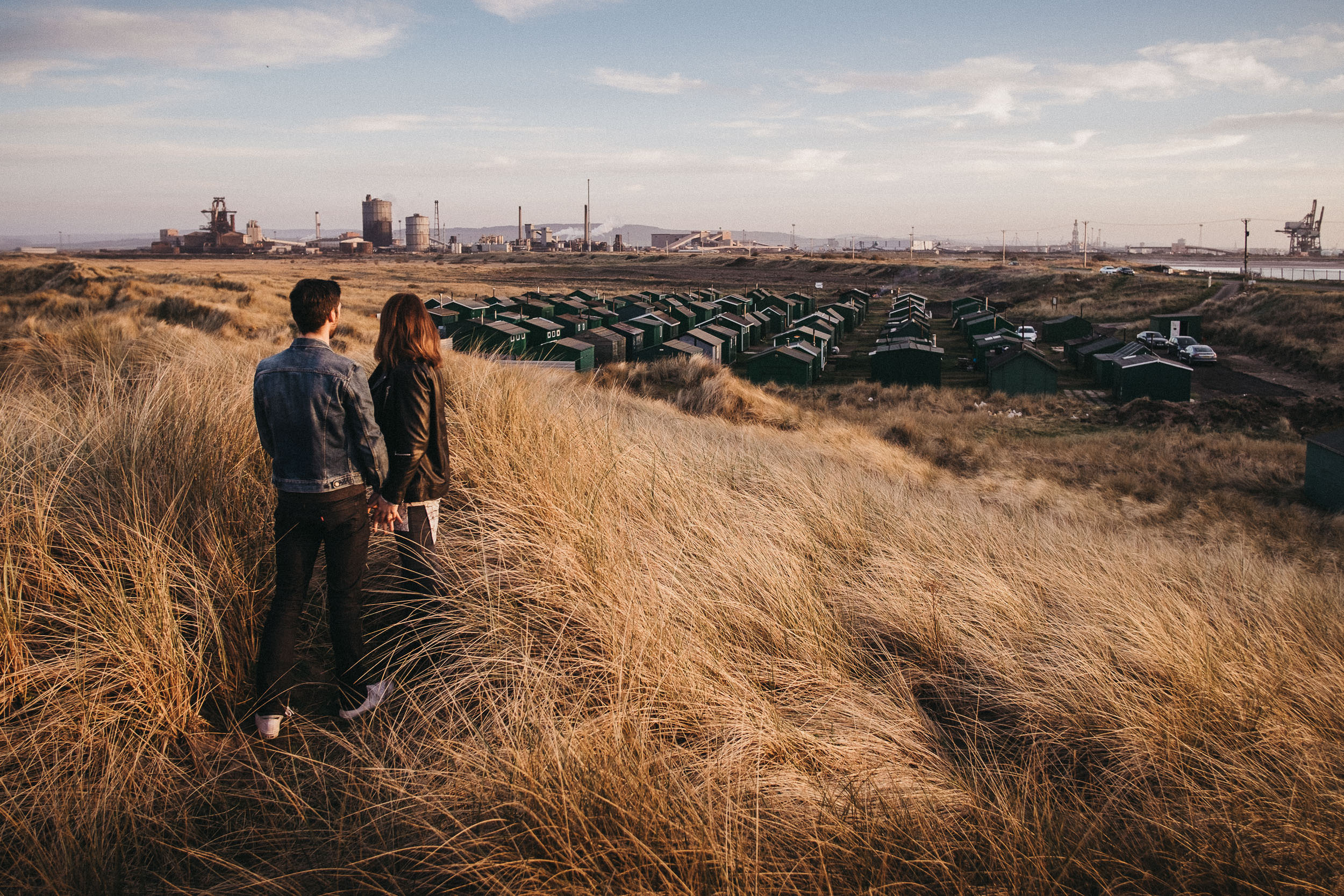Engaged couple look out over fisherman's huts and steelworks on Teeside