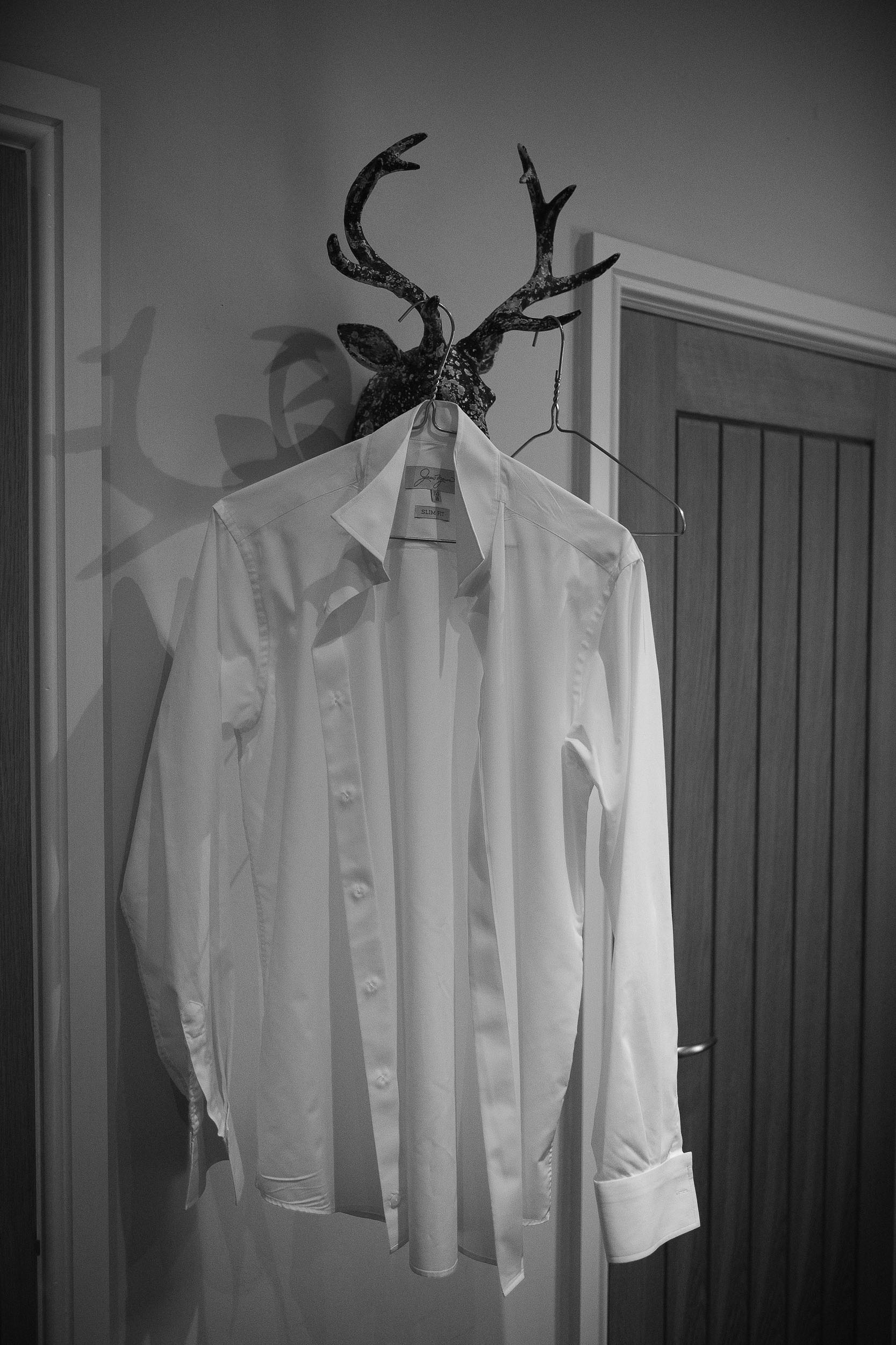 Black and white photo of groom's shirt hanging on antlers