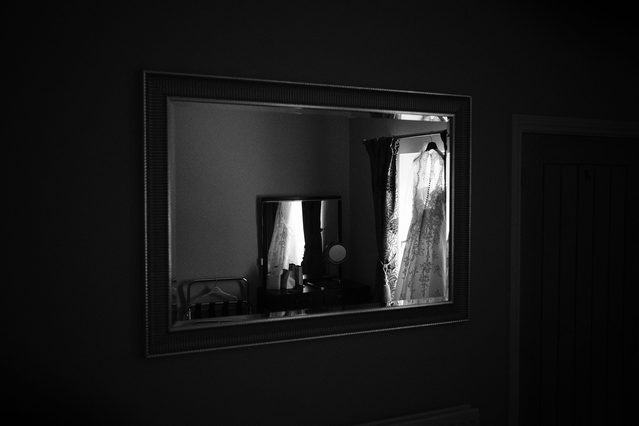 Black and white photo of dress hanging in window reflected in mirror