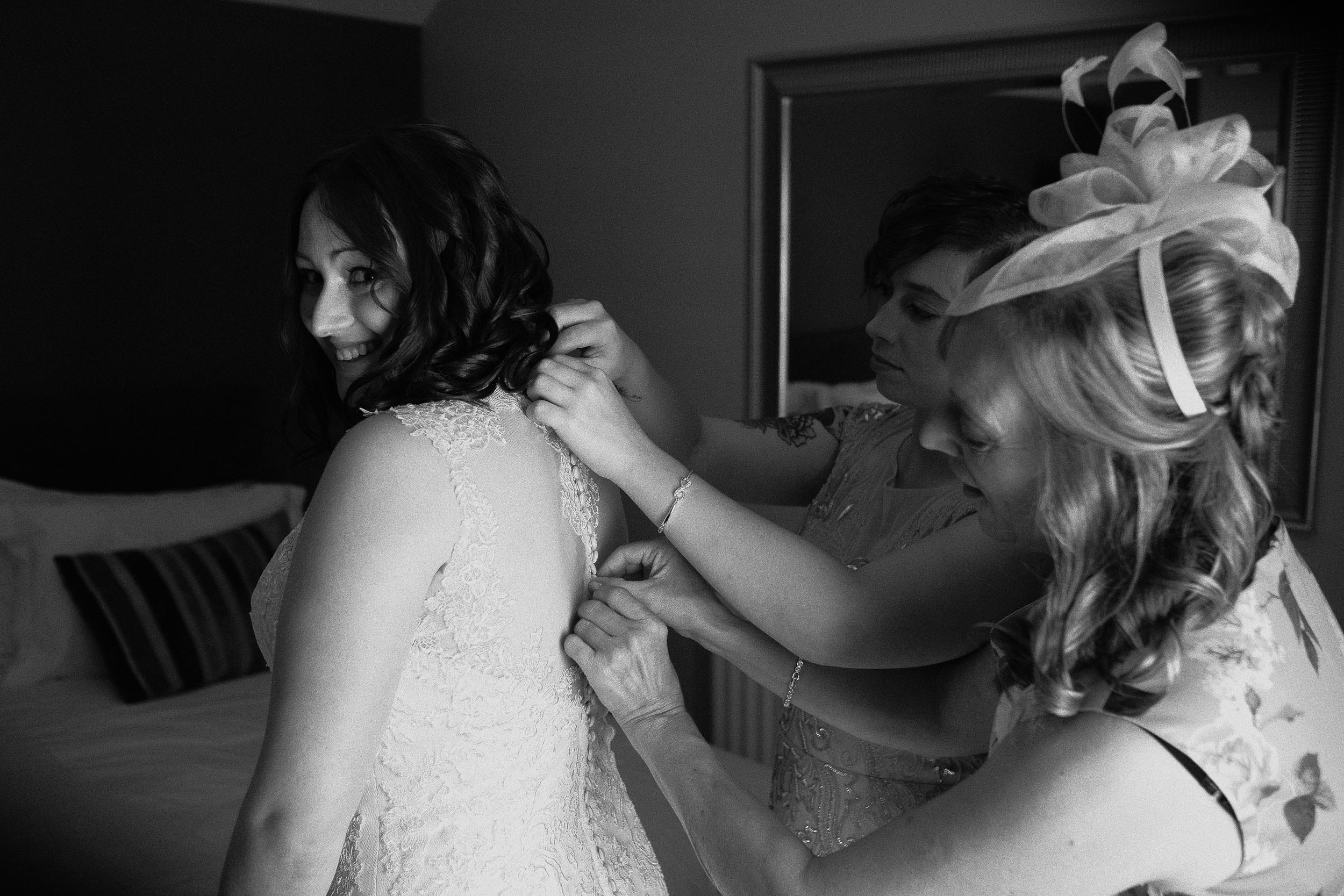 Black and white photo of bridesmaids tying brides dress