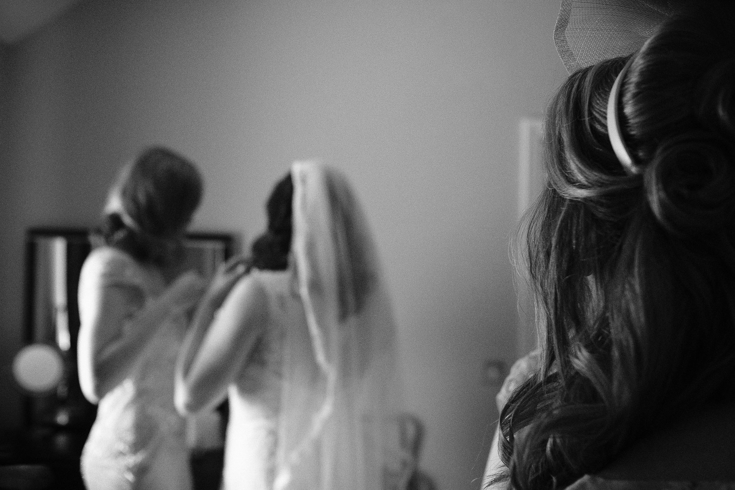 Black and white photo of the mother of the bride watching daughter get into wedding dress