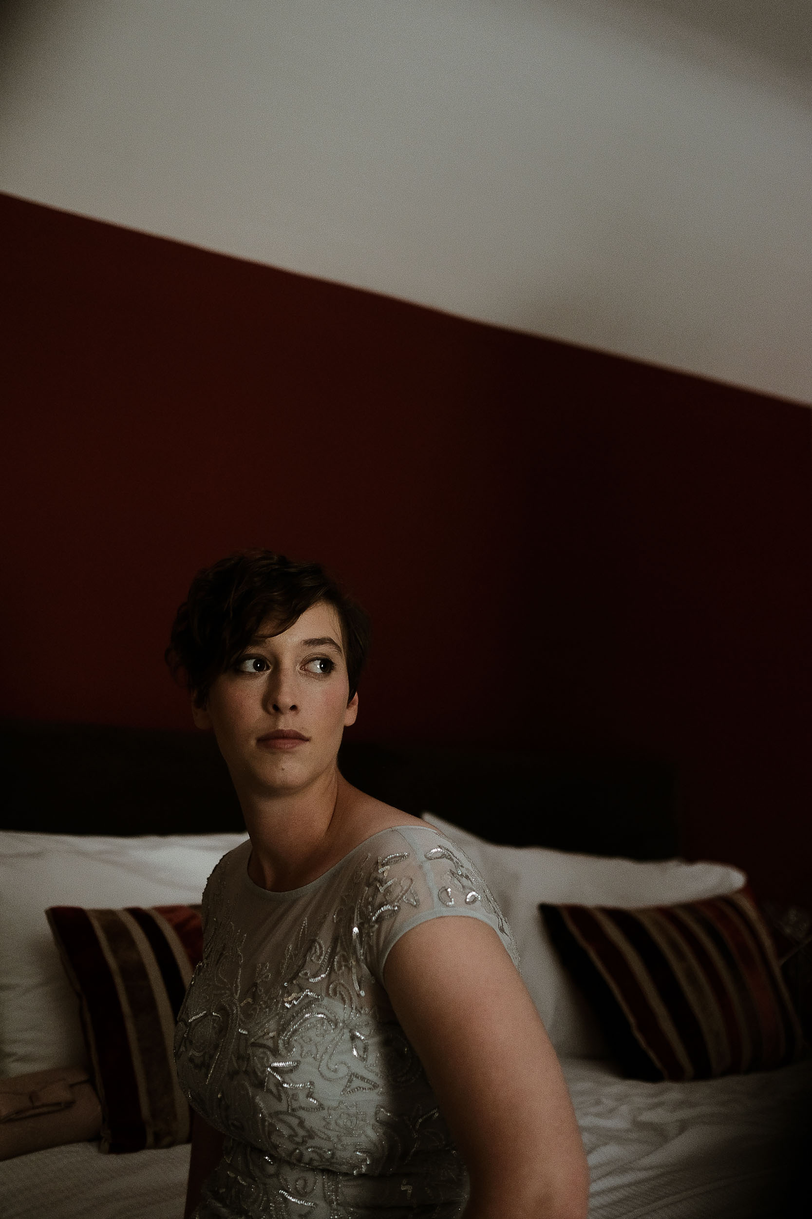 Bridesmaid sitting on bed with red wall behind