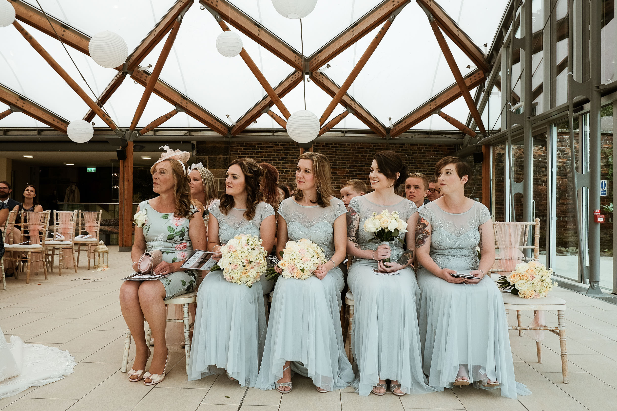 Bridesmaids look on during wedding ceremony