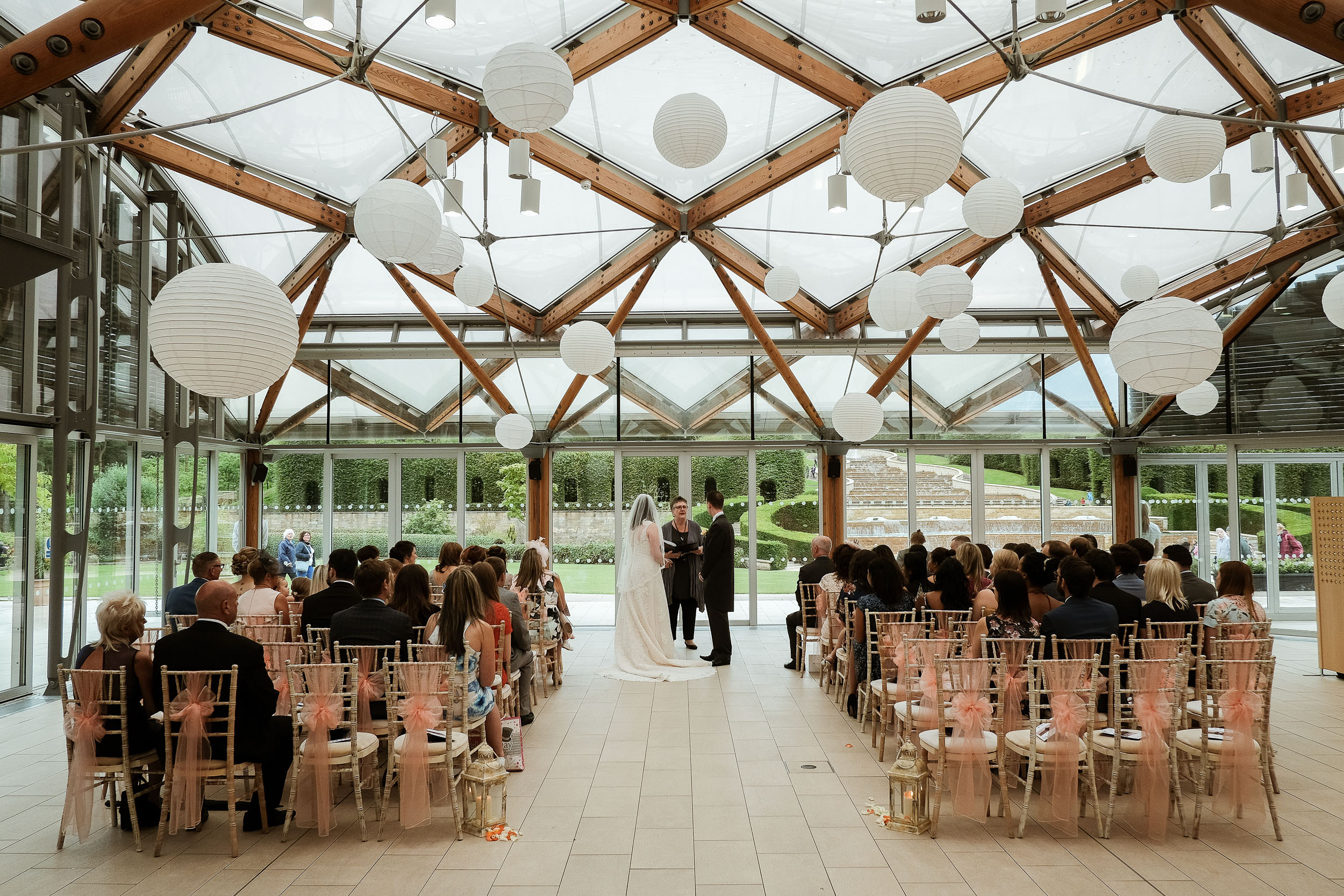 Wide shot of bride and groom and wedding party at the Alnwick Garden wedding ceremony